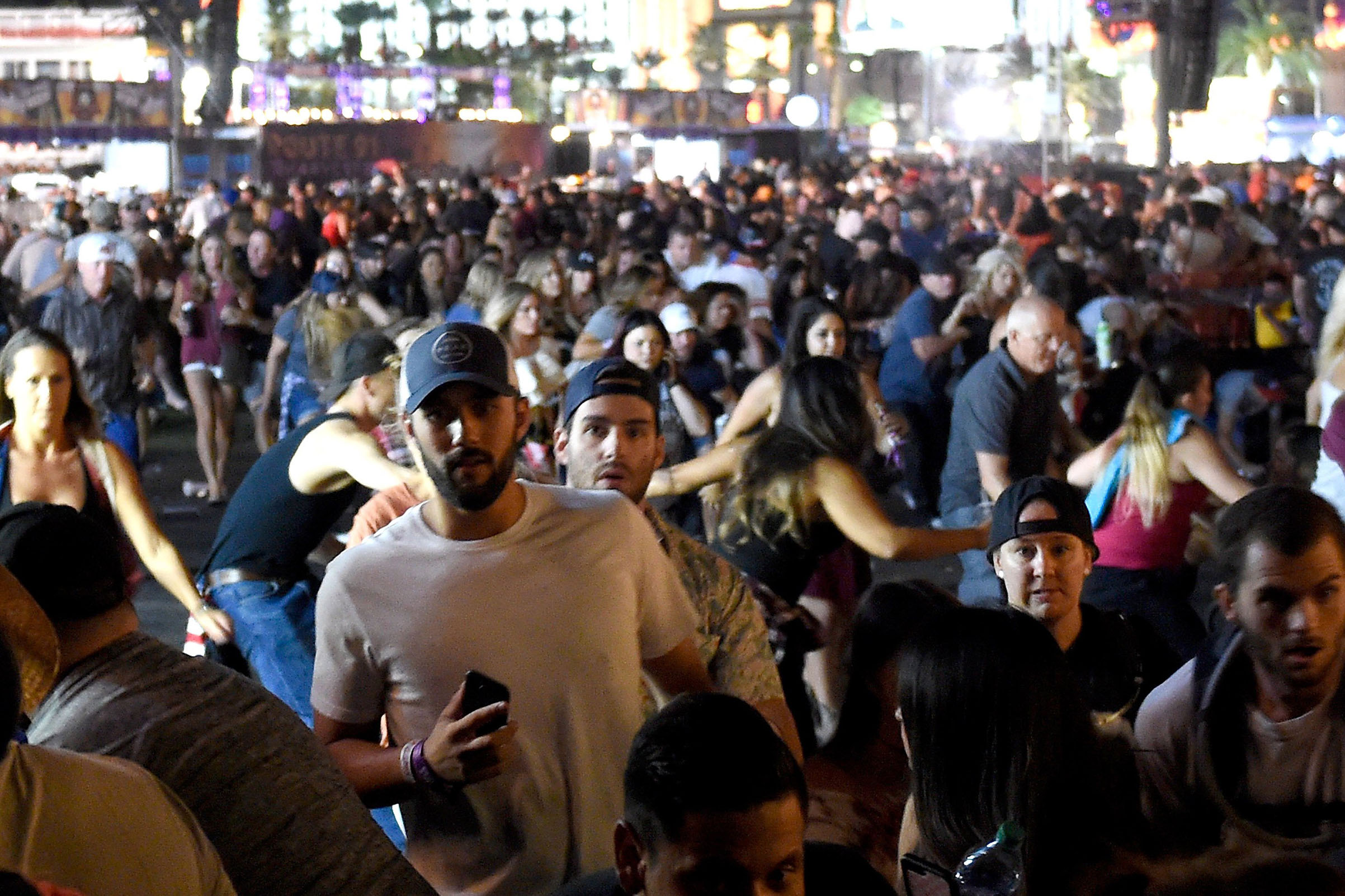 People flee the Route 91 Harvest country music festival grounds after a active shooter was reported on Oct. 1, 2017 in Las Vegas.