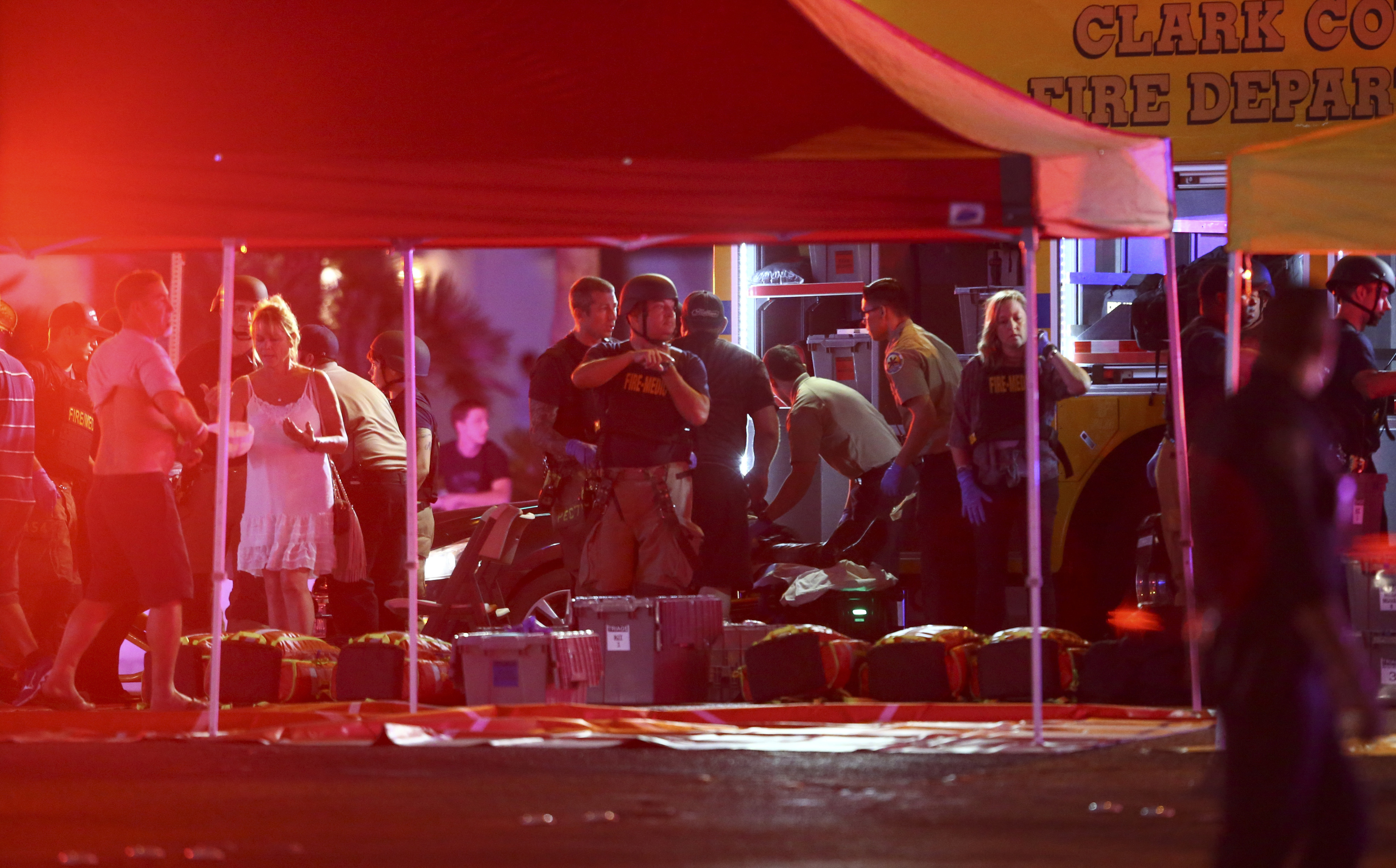 In this Oct. 1, 2017 file photo, medics treat the wounded as Las Vegas police respond during an active shooter situation on the Las Vegas Strip in Las Vegas.