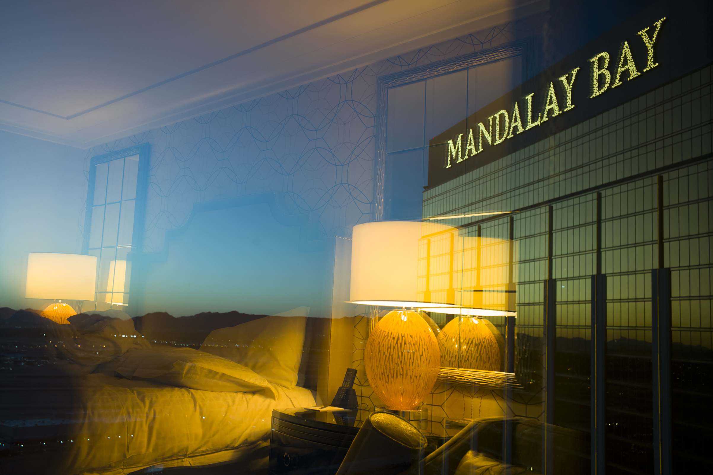 Photographer's hotel room is reflected on to the window that he is shooting through, on the other side of the glass is the Mandalay Bay Hotel sign, Oct. 3, 2017.