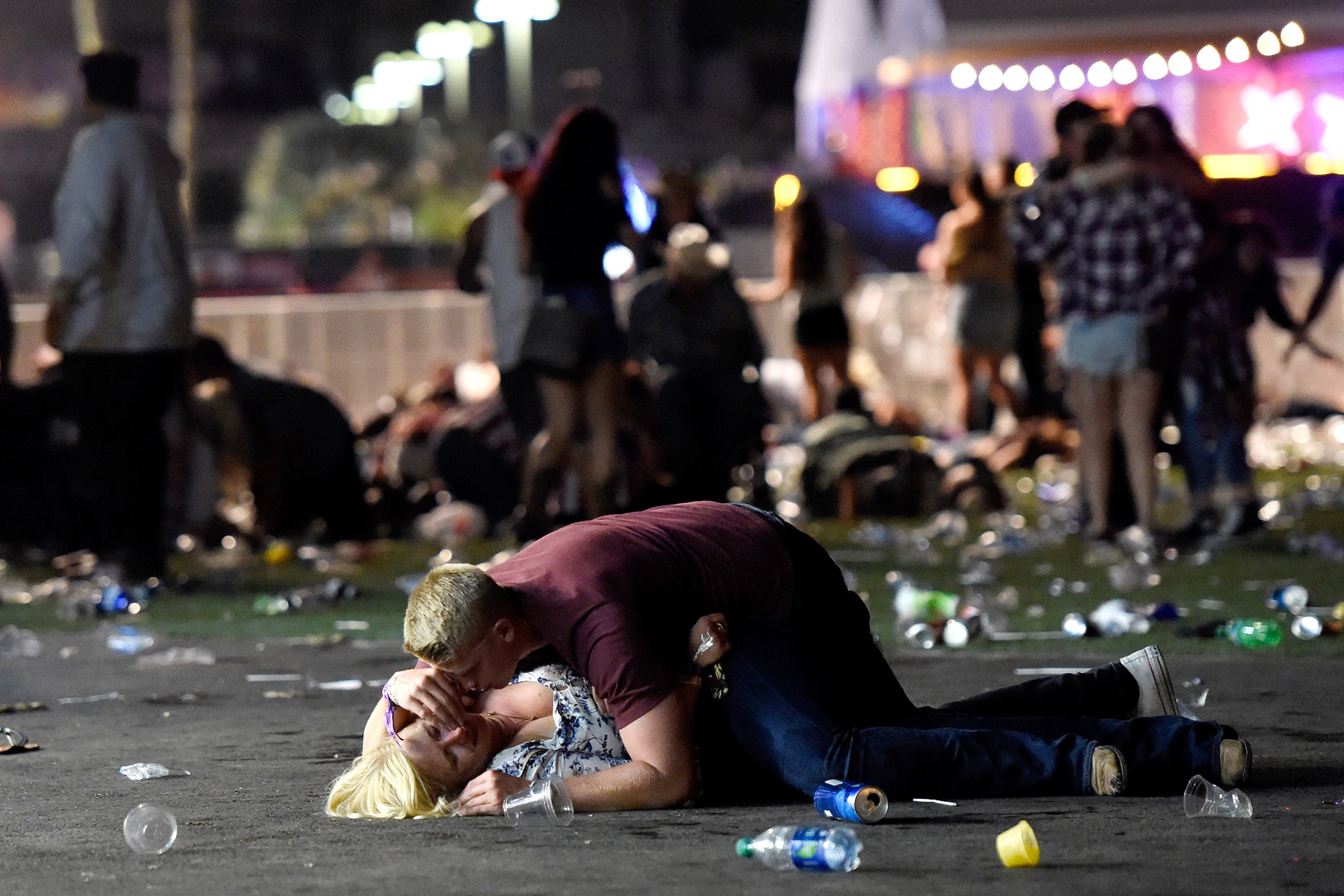A man lays on top of a woman as others flee the Route 91 Harvest country music festival grounds after a active shooter was reported at Mandalay Bay on Oct. 1, 2017 in Las Vegas.