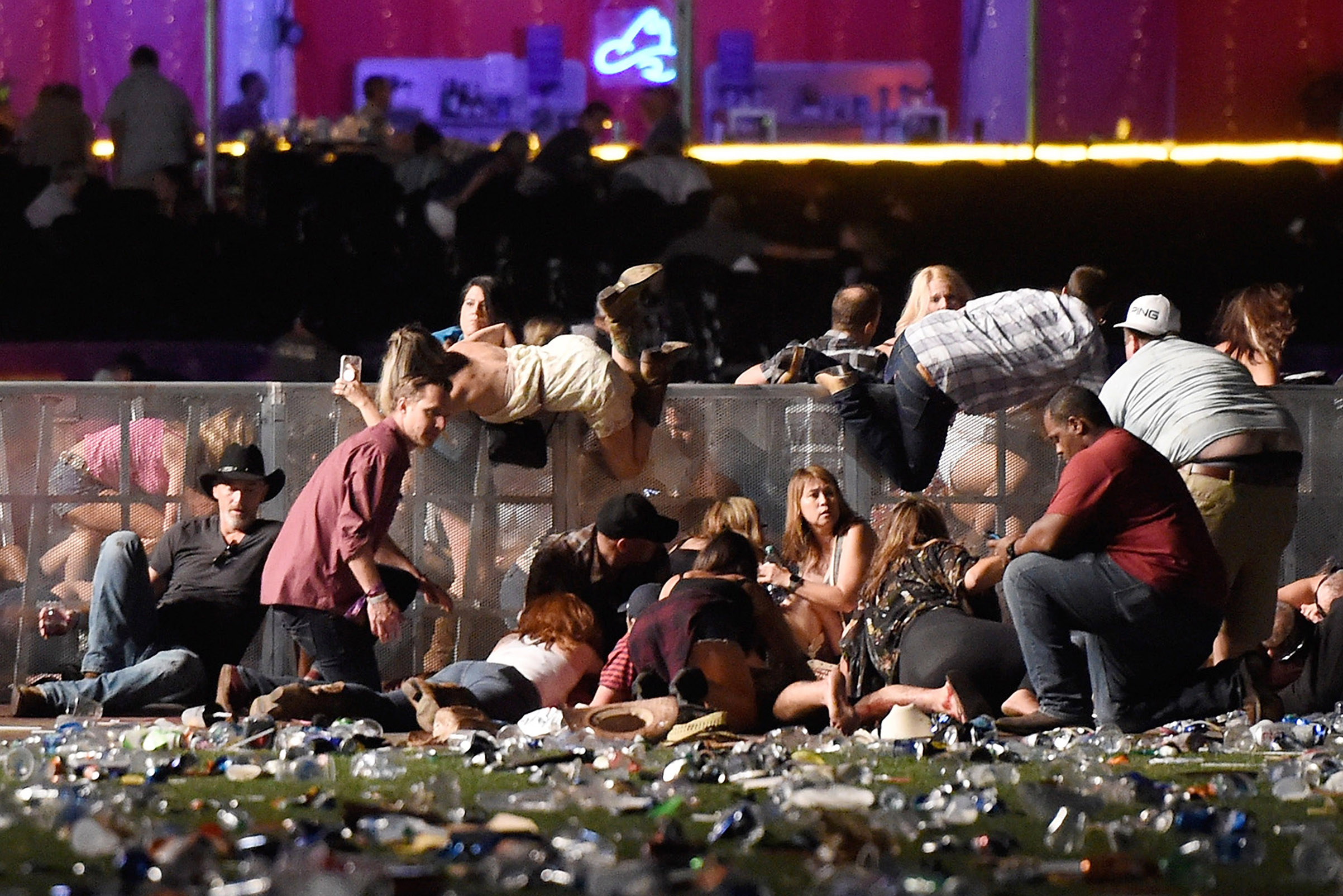 People scramble for shelter at the Route 91 Harvest country music festival after a shooting, Oct. 1, 2017 in Las Vegas.