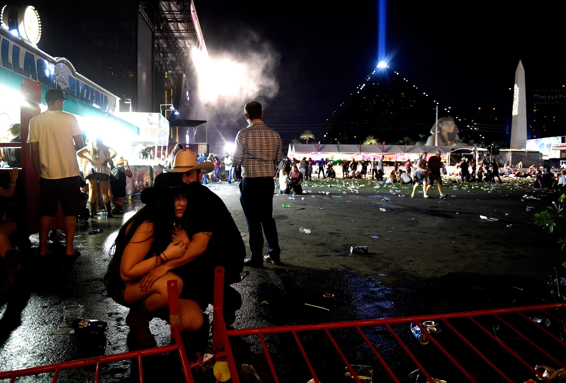 A couple takes cover at the Route 91 Harvest country music festival after apparent gun fire was heard on Oct. 1, 2017 in Las Vegas.