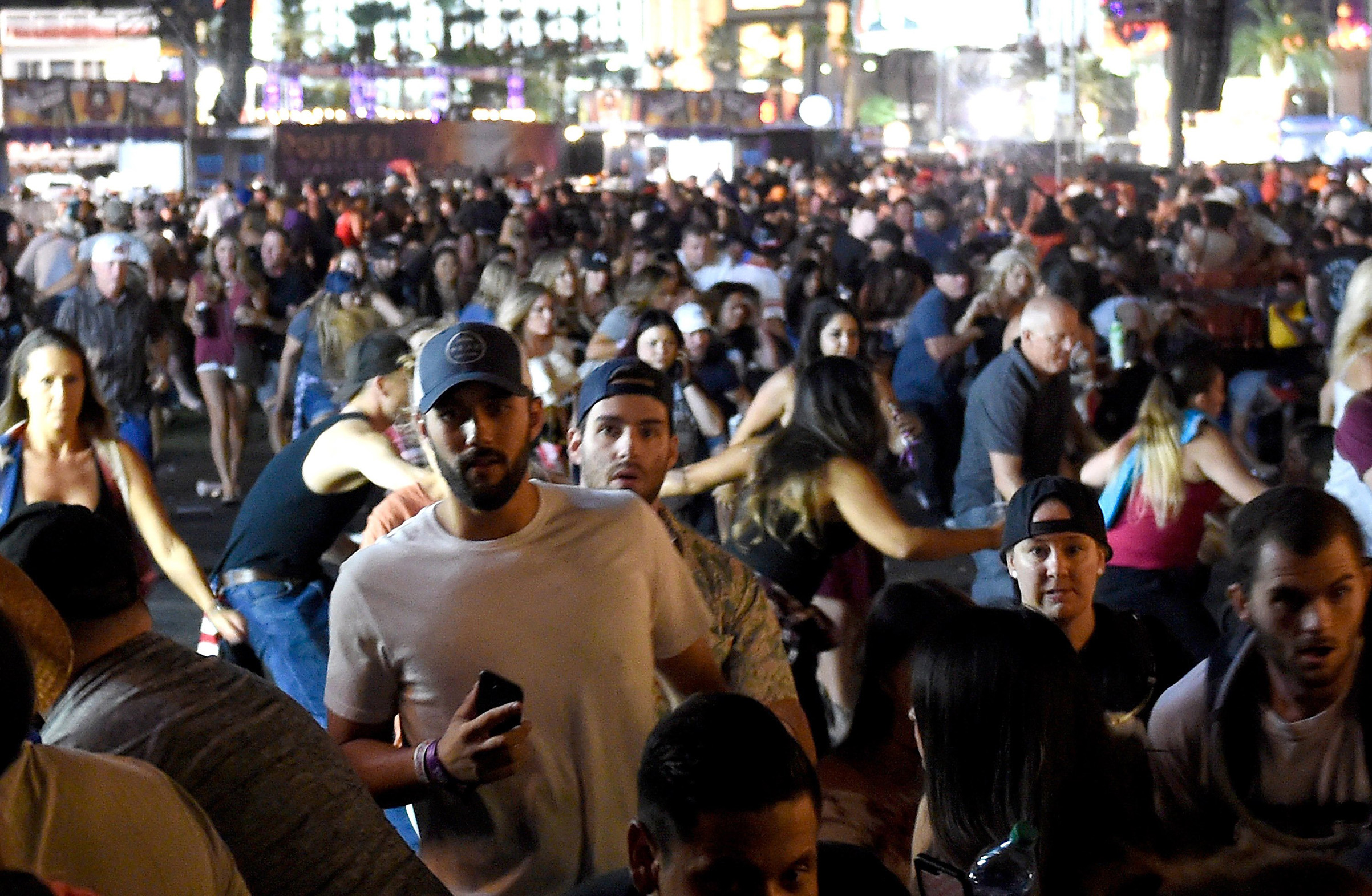 People flee the Route 91 Harvest country music festival grounds after apparent gun fire was heard, Oct. 1, 2017 in Las Vegas.