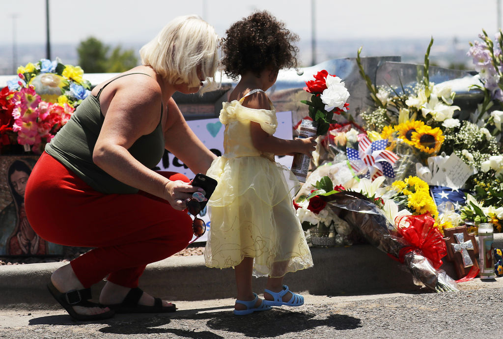 Jessica (L) and Kalani Windham leave flowers and a candle outside the Walmart that was the scene of a mass shooting in El Paso, Texas.