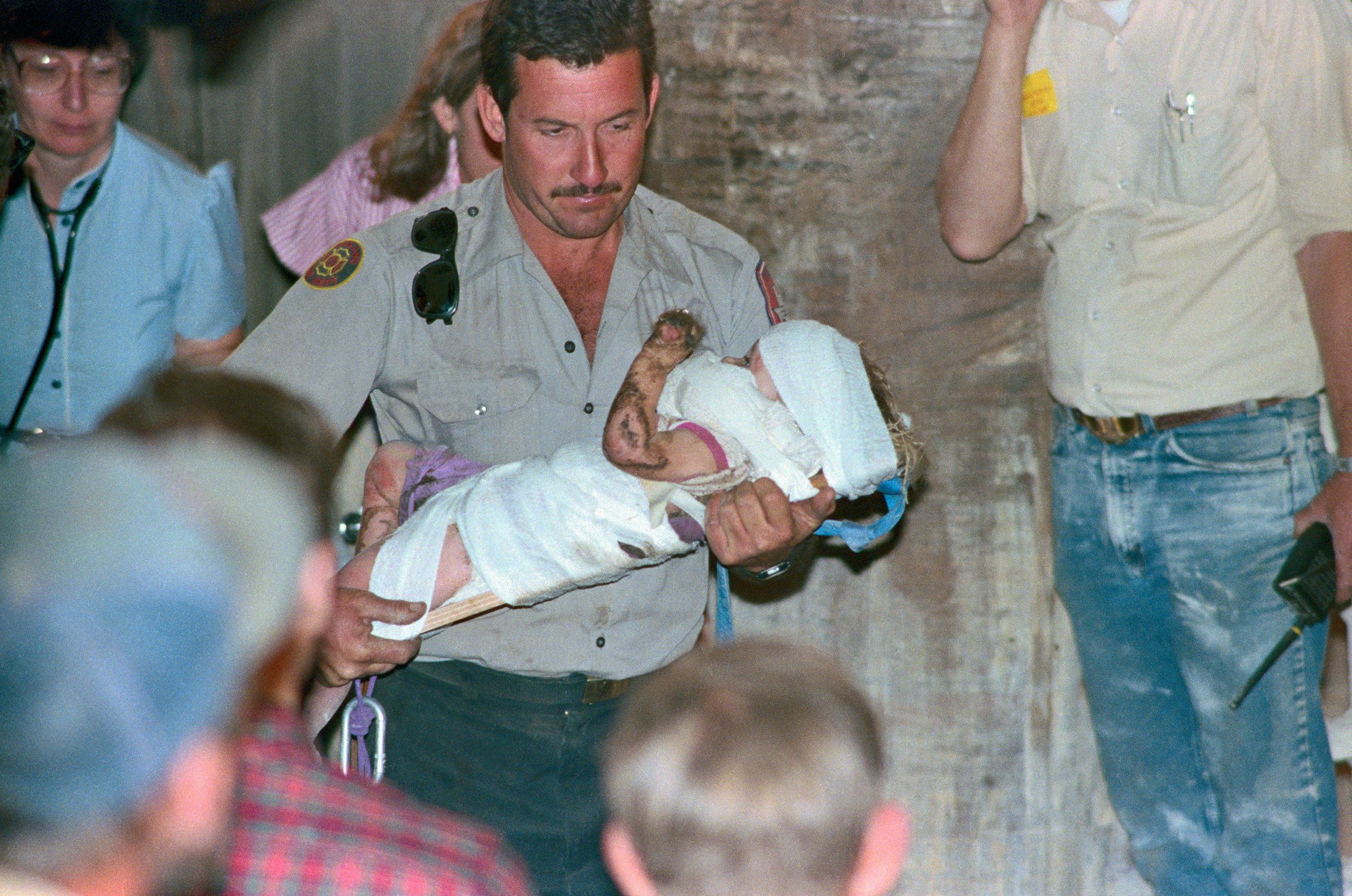 Rescuer rushes baby rescued from fall into a well where lay for three days before she was rescued, Oct. 16, 1987.