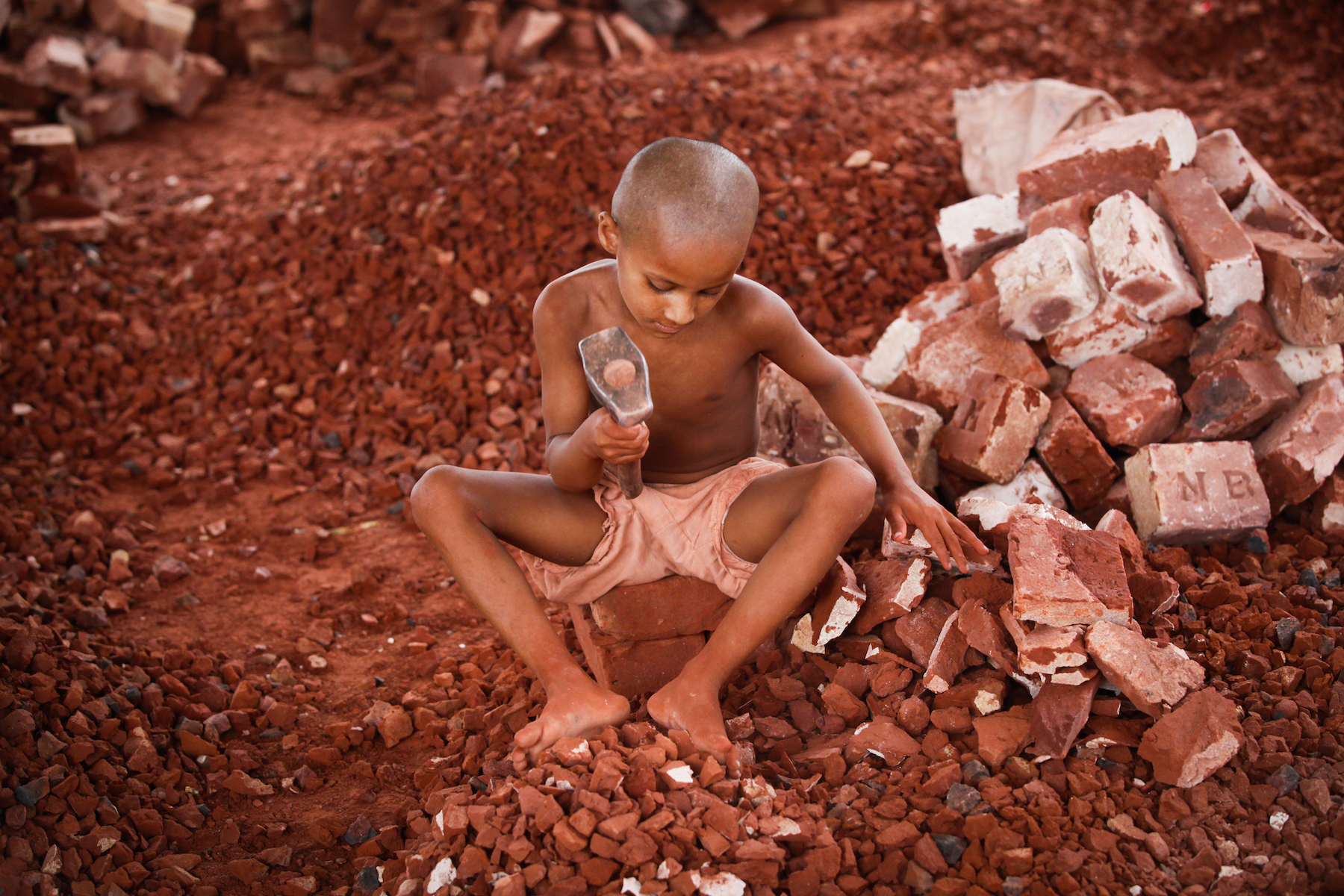 A Bangladeshi child break bricks at Postogola brick breaking yard in Dhaka, Bangladesh, on June 3, 2017