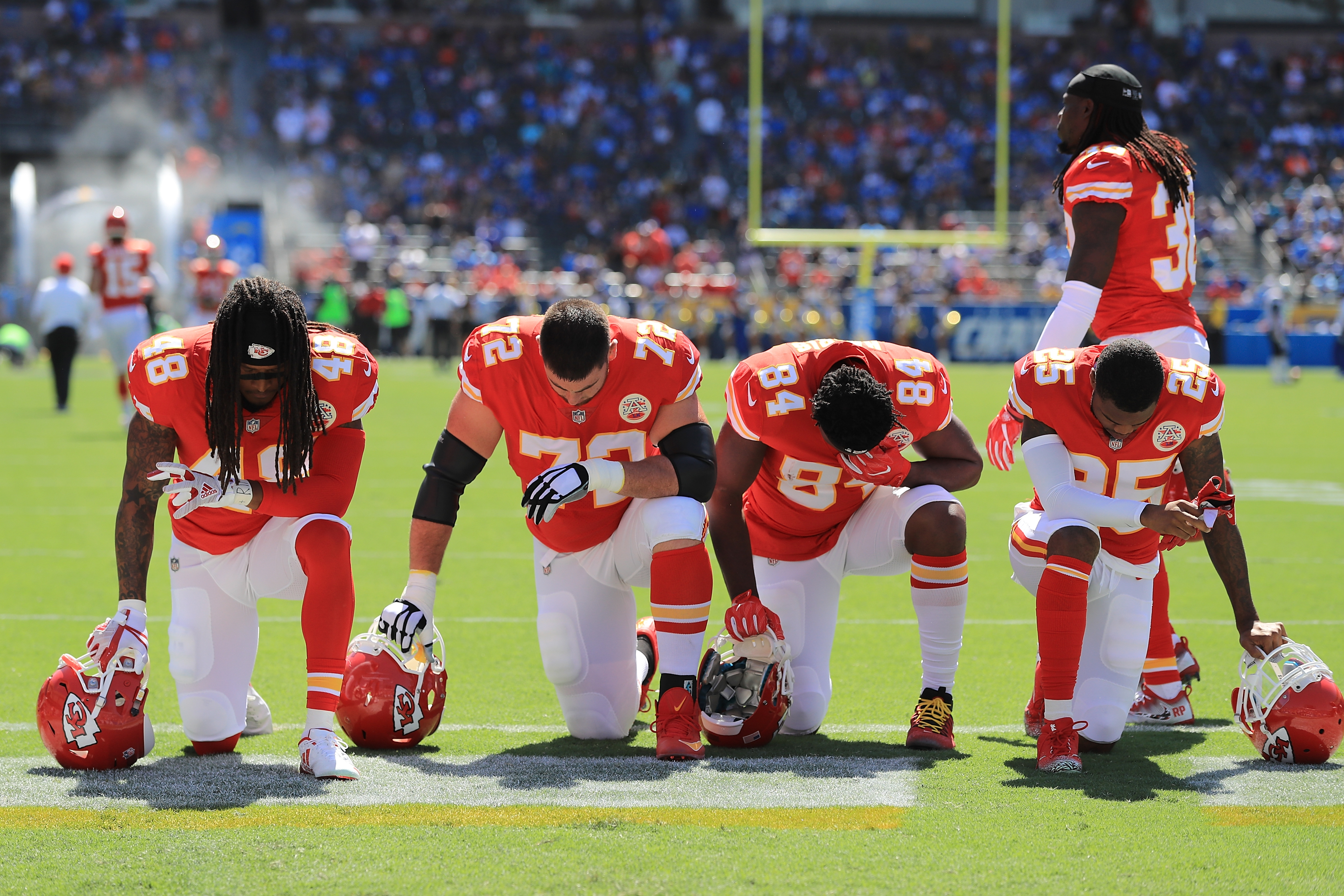 Football players Terrance Smith #48, Eric Fisher #72, Demetrius Harris #84, and Cameron Erving #75 of the Kansas City Chiefs is seen taking a knee before the game against the Los Angeles Chargers at the StubHub Center on September 24, 2017 in Carson, California.