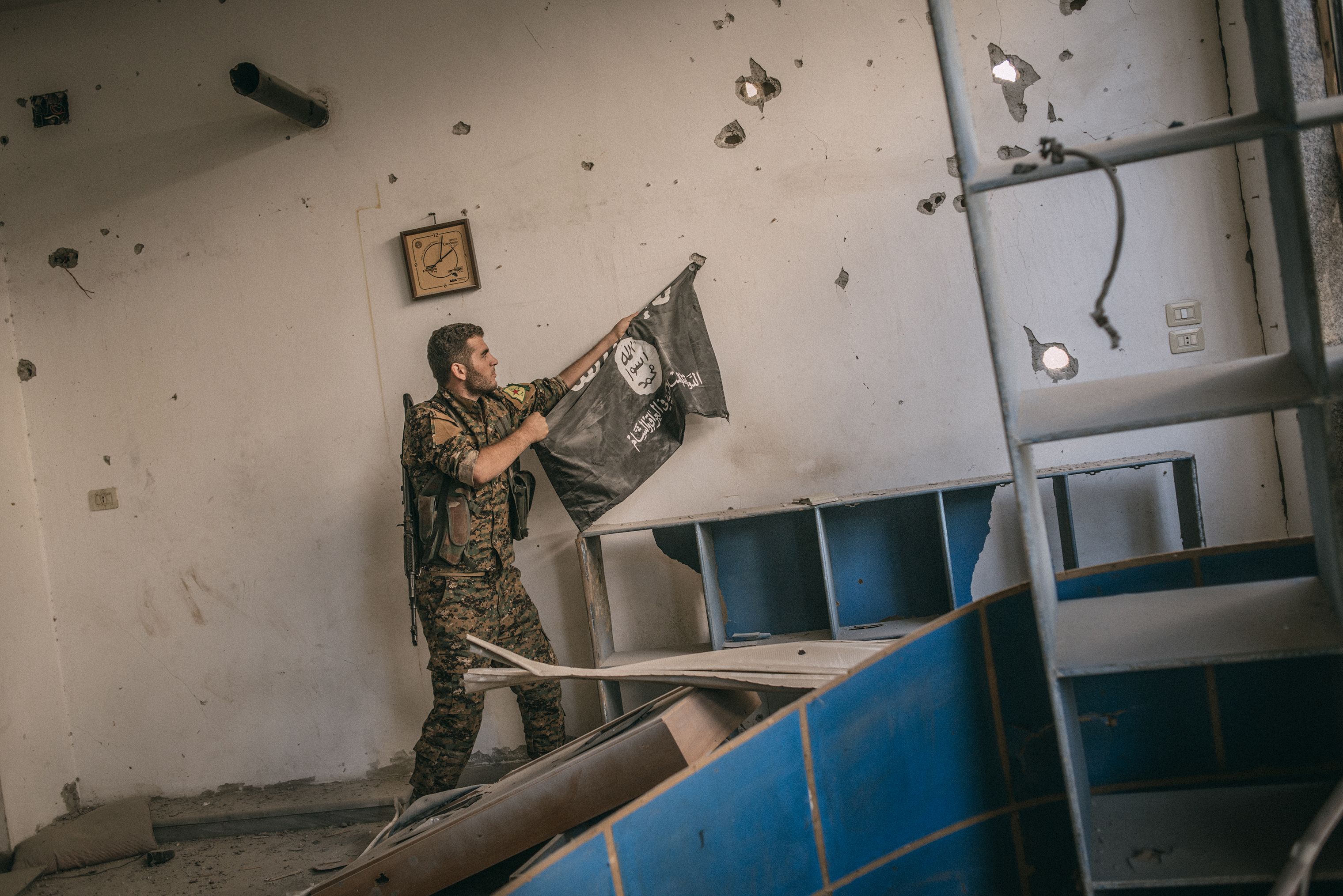 A member of the Syrian Democratic Forces removes an Islamic State flag from a wall on Oct. 18, 2017.
