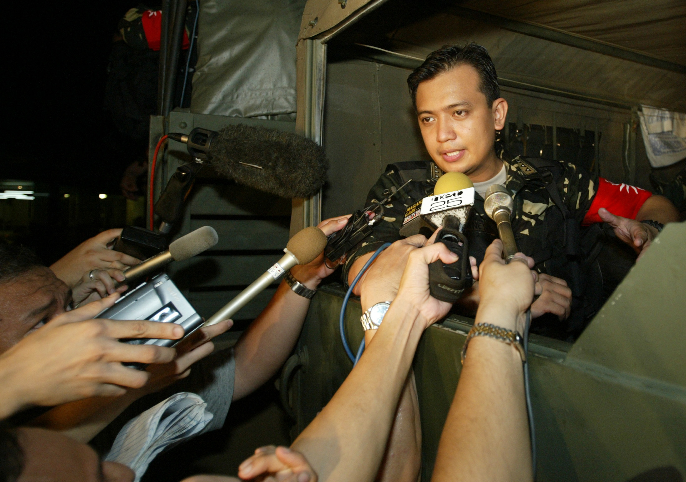 Navy Lieutenant Antonio Trillanes, then a mutiny leader, speaks to journalists after the end of a seige of a Manila shopping centre July 27, 2003.