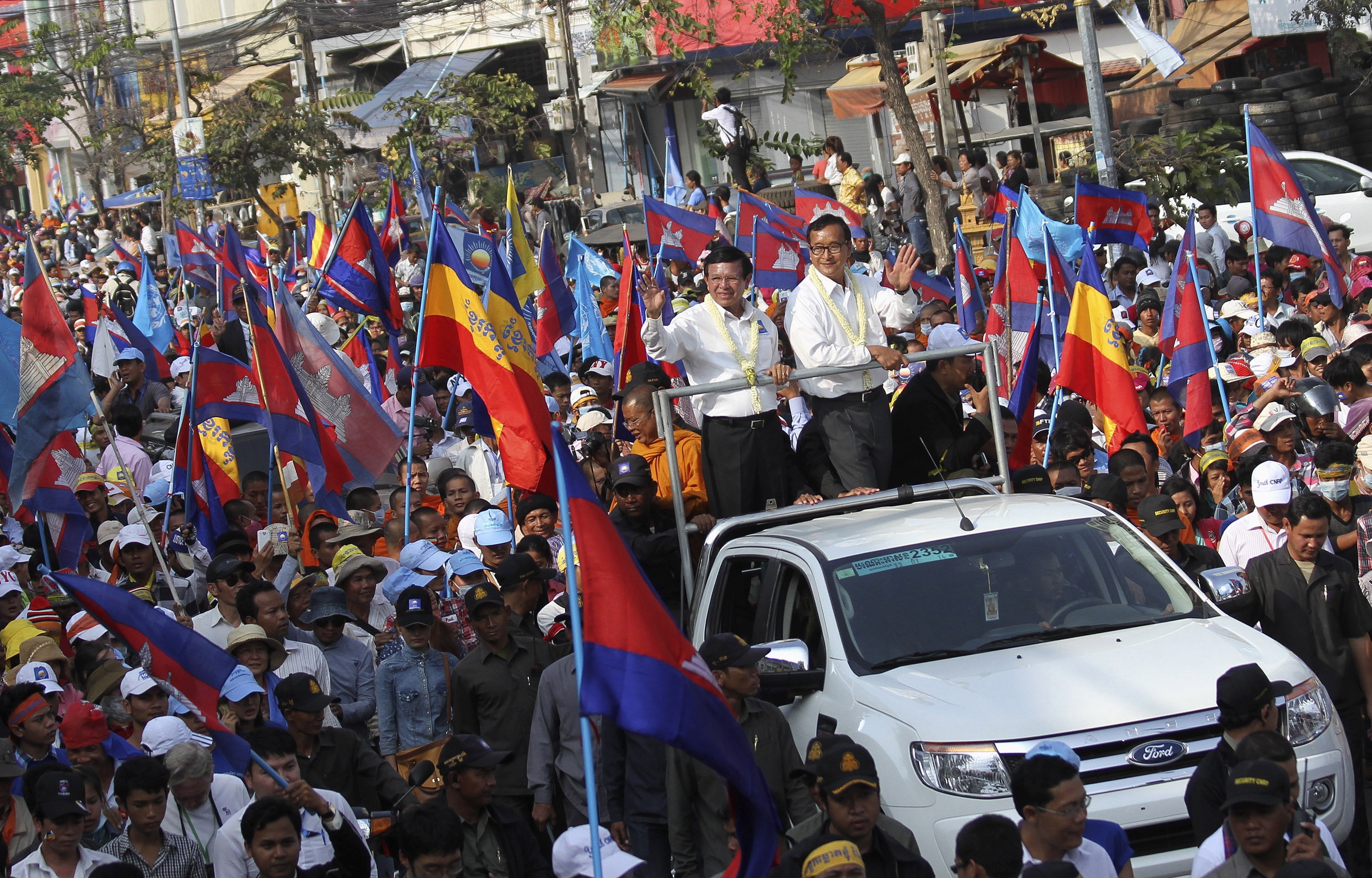 Sam Rainsy president of the opposition Cambodian National Rescue Party (CNRP) and party vice-president Kem Sokha, greet supporters during a protest in Phnom Penh Dec. 29, 2013.