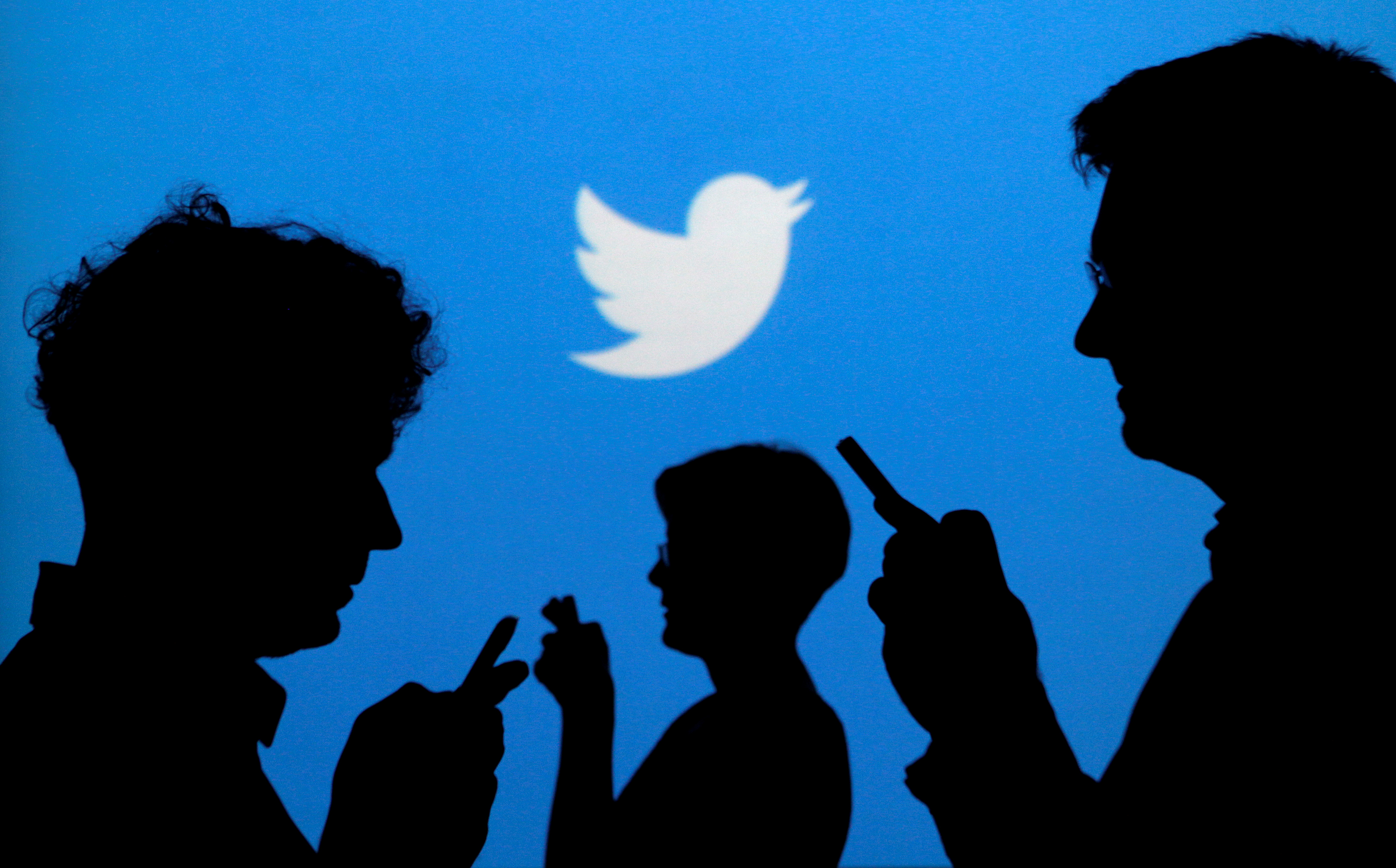 Smartphone users are silhouetted against a backdrop with the Twitter logo in Warsaw, Poland on Sept. 27, 2013.