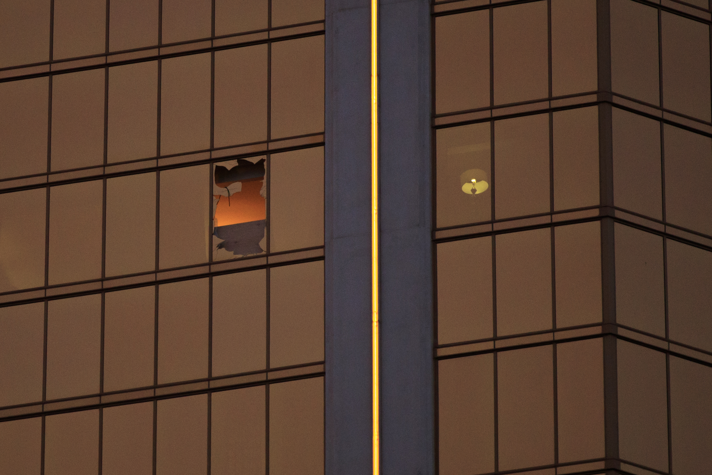 A window is broken on the 32nd floor of the Mandalay Bay Resort and Casino where a gunman opened fire on a concert crowd on Sunday night, Oct. 3, 2017 in Las Vegas.