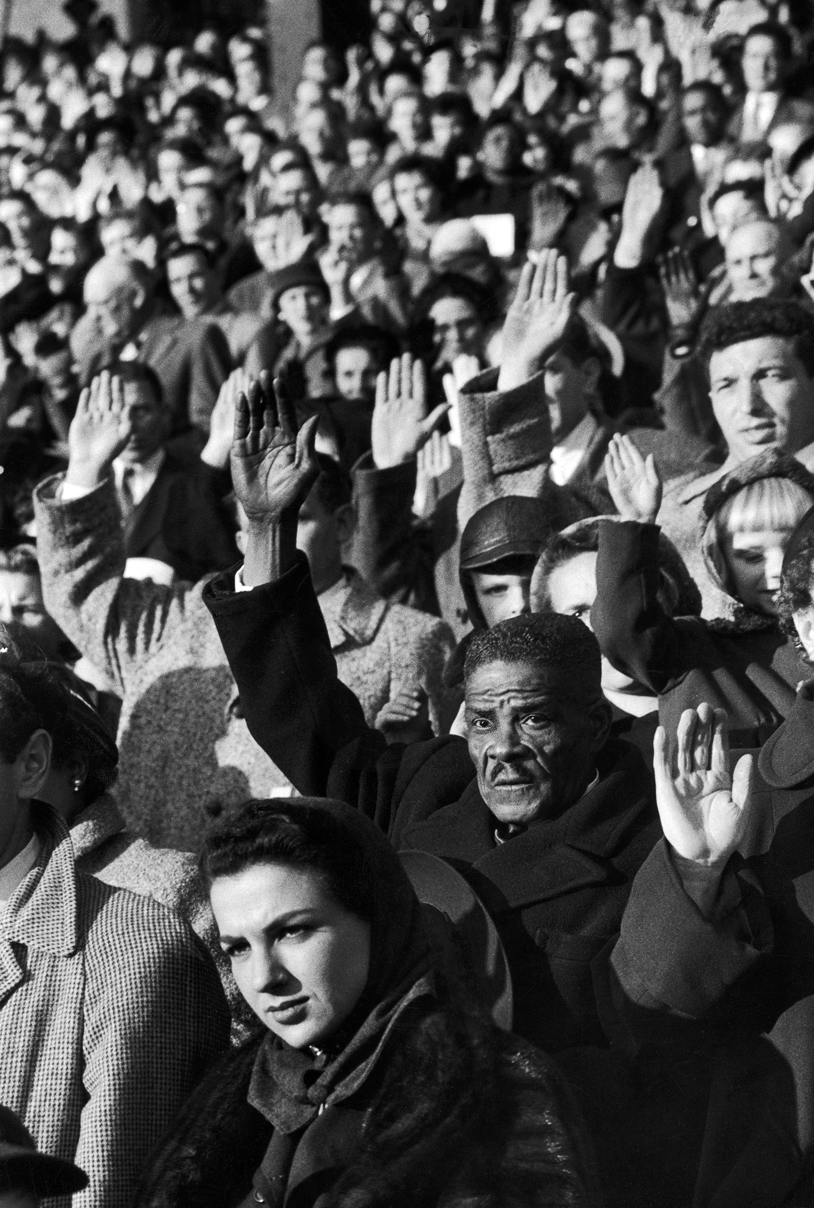 Caption from LIFE. In mass induction of 9,000 new citizens, men and women at New York's Polo Grounds raise their right hands to take oath of allegiance.