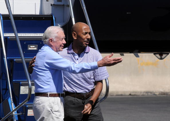 Former U.S. President Jimmy Carter steps off a plane with Aijalon Mahli Gomes at Logan International Airport in Boston, Massachusetts on August 27, 2010.