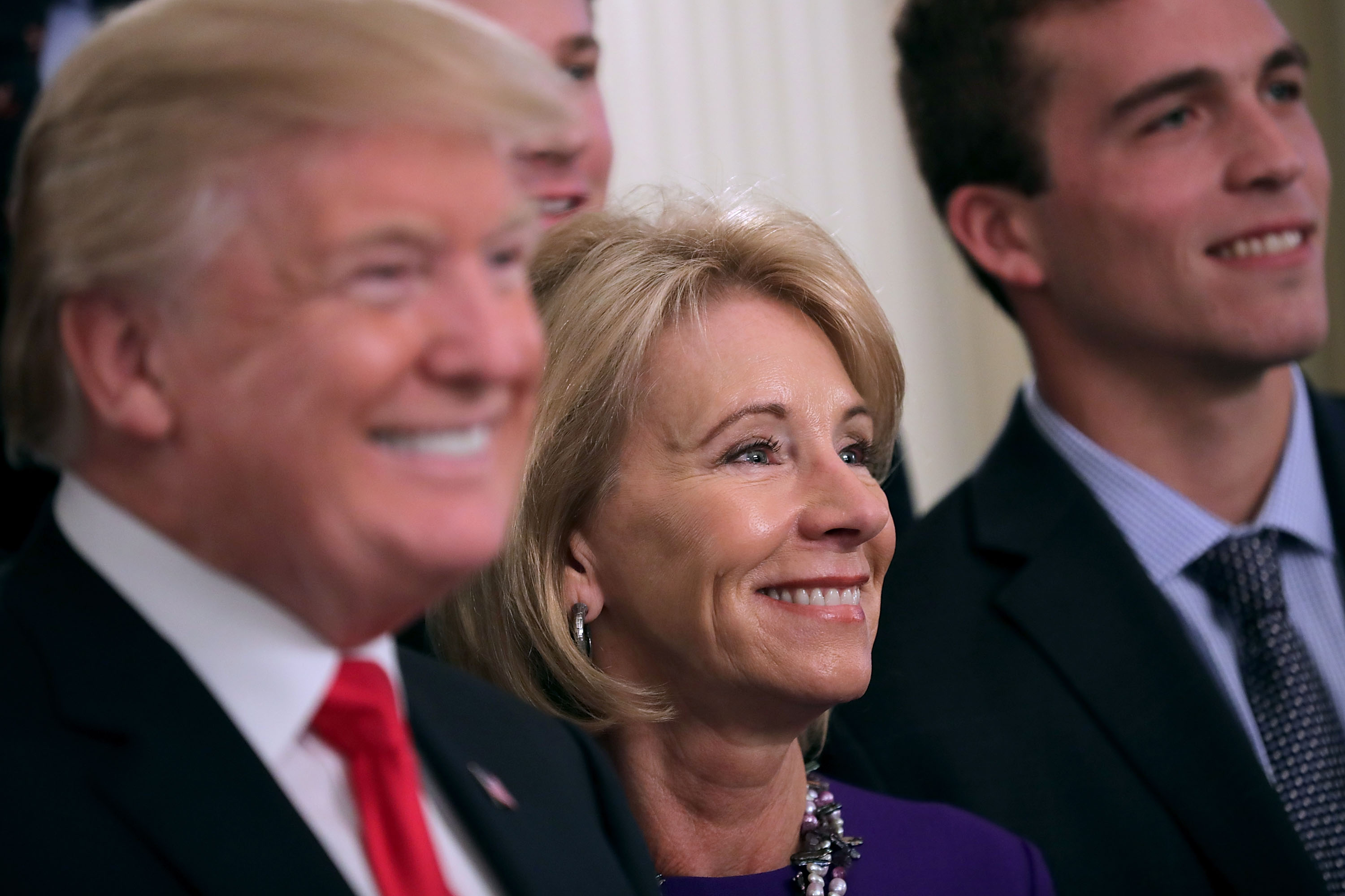 President Donald Trump and Education Secretary Betsy Devos pose for photographs with members of the National Collegiate Athletic Association's champion University of Virginia men's tennis team in the East Room of the White House on Nov. 17, 2017 in Washington, D.C.