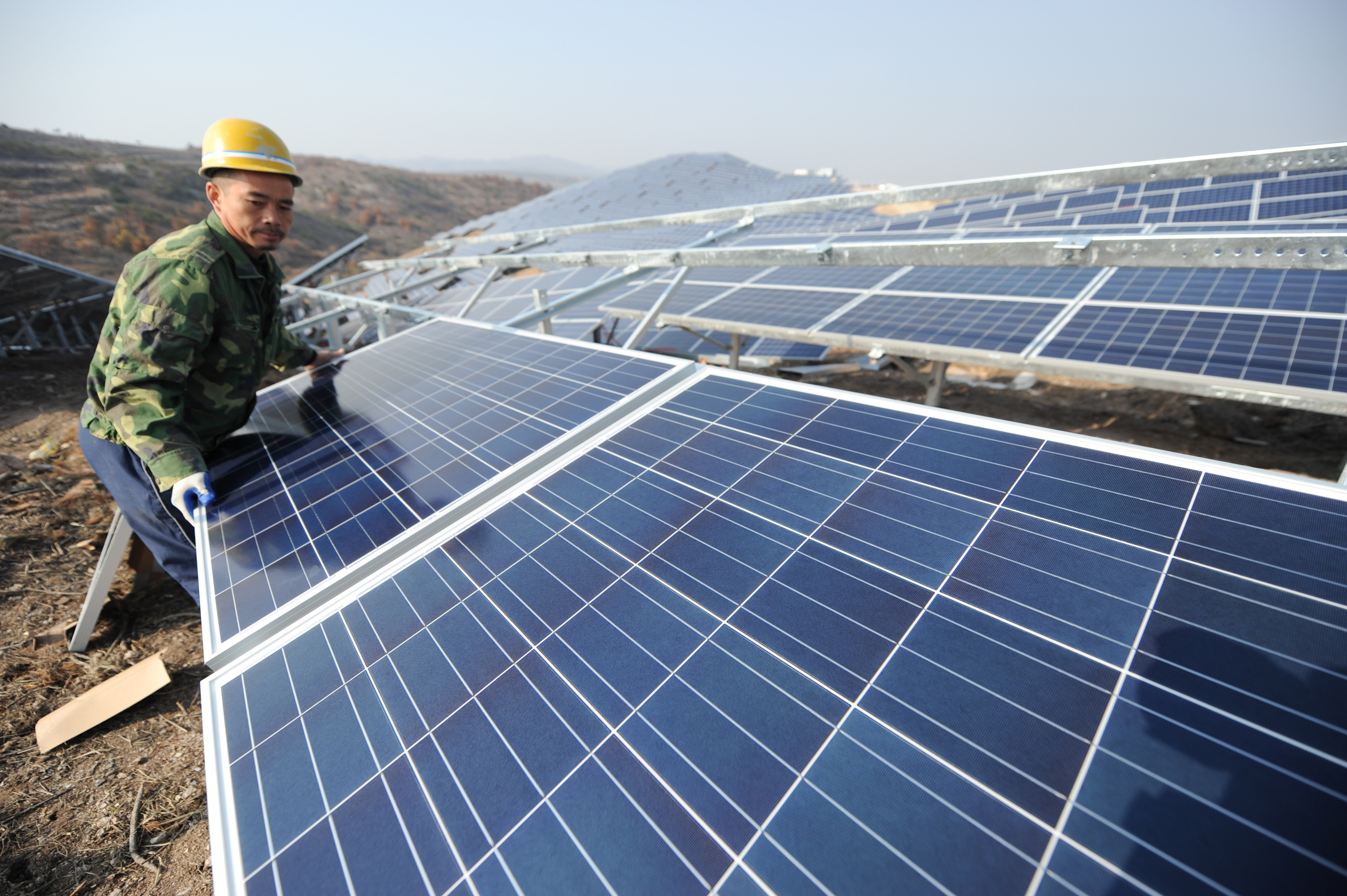 A worker installs polycrystalline silicon solar panels as terrestrial photovoltaic power project starts in 2015 in Yantai, Shandong Province of China.