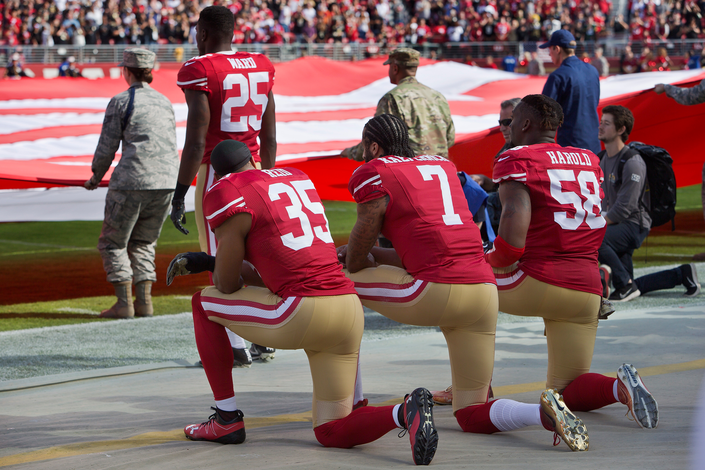 Quarterback Colin Kaepernick #7, safety Eric Reid #35, and linebacker Eli Harold #58 of the San Francisco 49ers kneel before a game against the New Orleans Saints with the U.S. flag unfurled in honor of the armed services on Nov. 6 2016 at Levi's Stadium in Santa Clara, Calif.