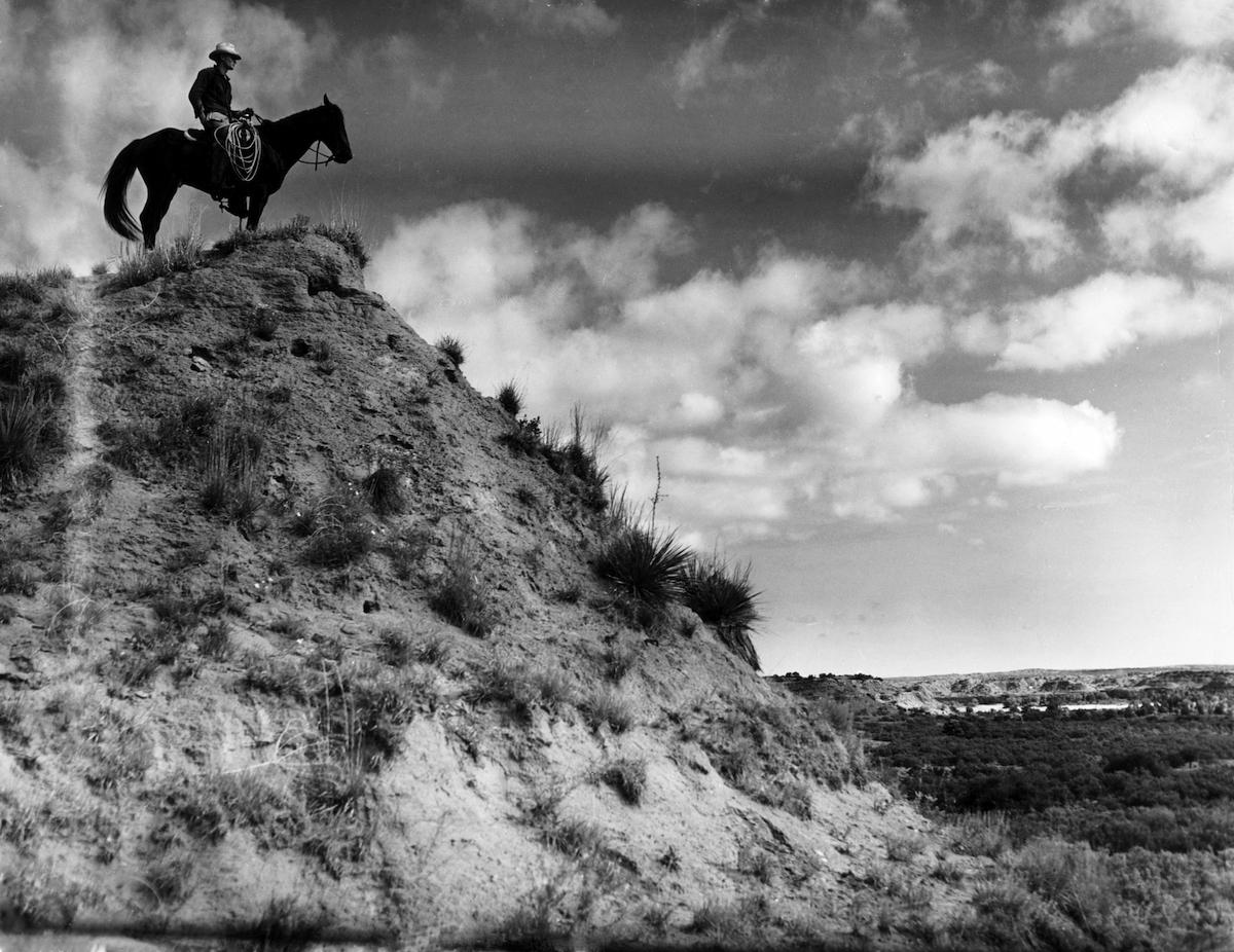 A cowboy on horseback at the Matador Ranch in 1940s Texas.