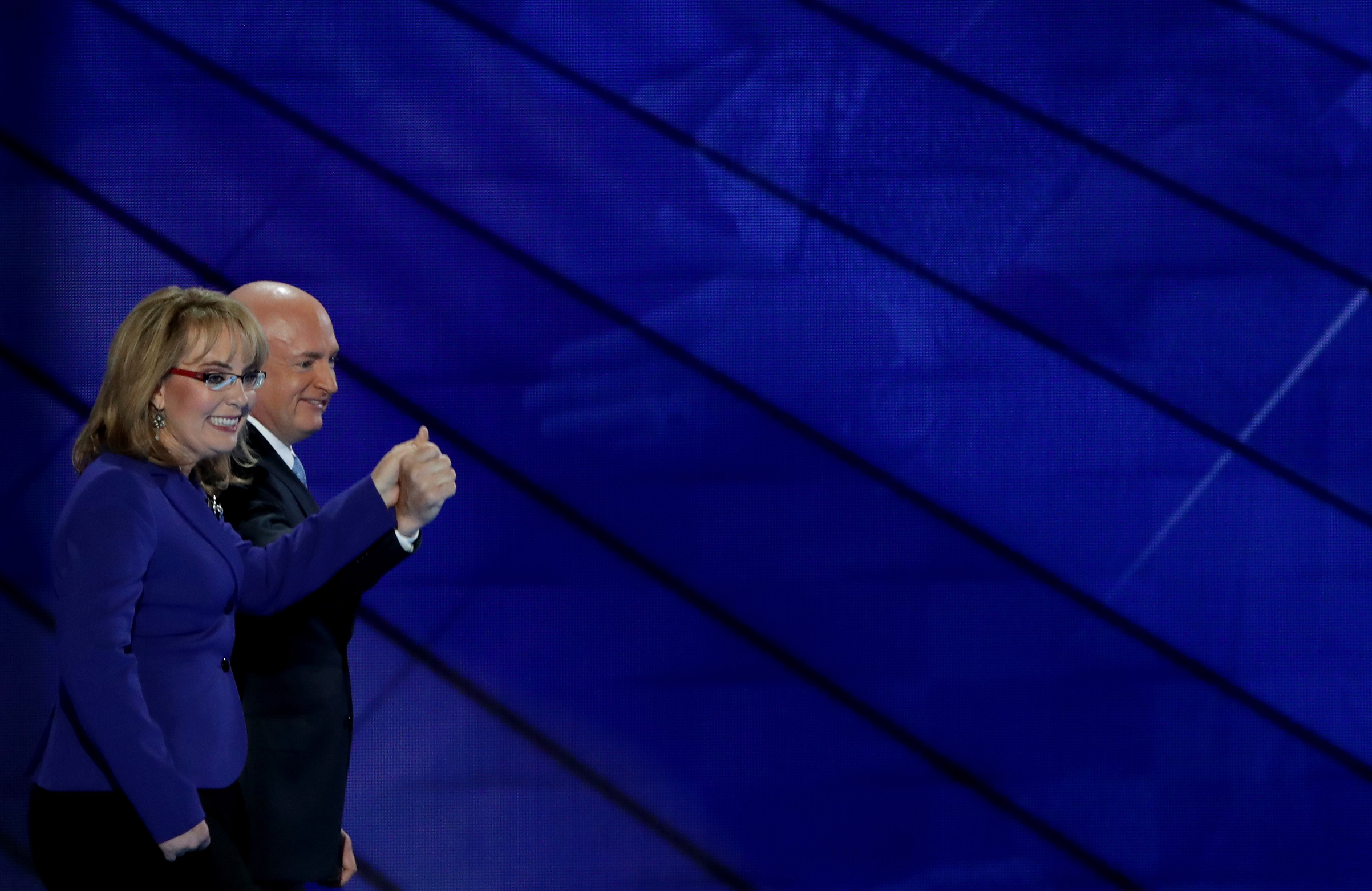 Former Congresswoman Gabby Giffords and her husband, retired NASA Astronaut and Navy Captain Mark Kelly, hold hands as they walk off stage on the third day of the Democratic National Convention, July 27, 2016 in Philadelphia.