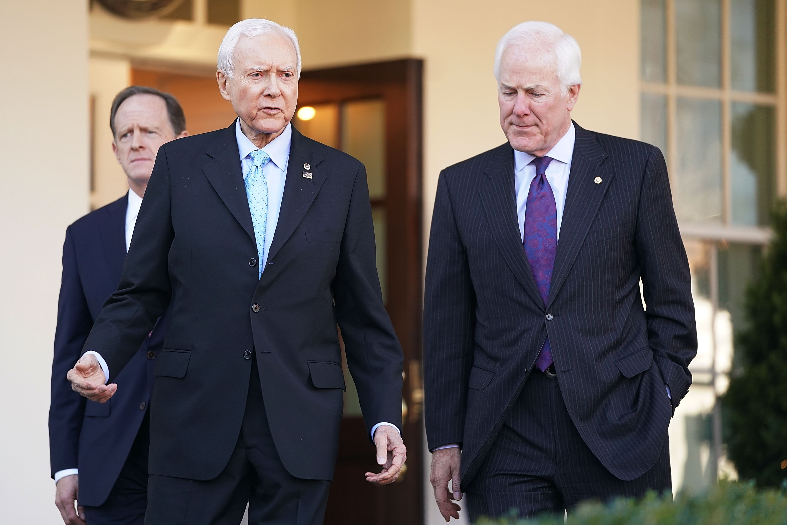 Senate Finance Committee members Sen. Pat Toomey (R-PA) (L) and Sen. John Cornyn (R-TX) (R) walk out of the West Wing with Chairman Orrin Hatch (R-UT) following a lunch meeting with U.S. President Donald Trump at the White House November 27, 2017 in Washington, DC.