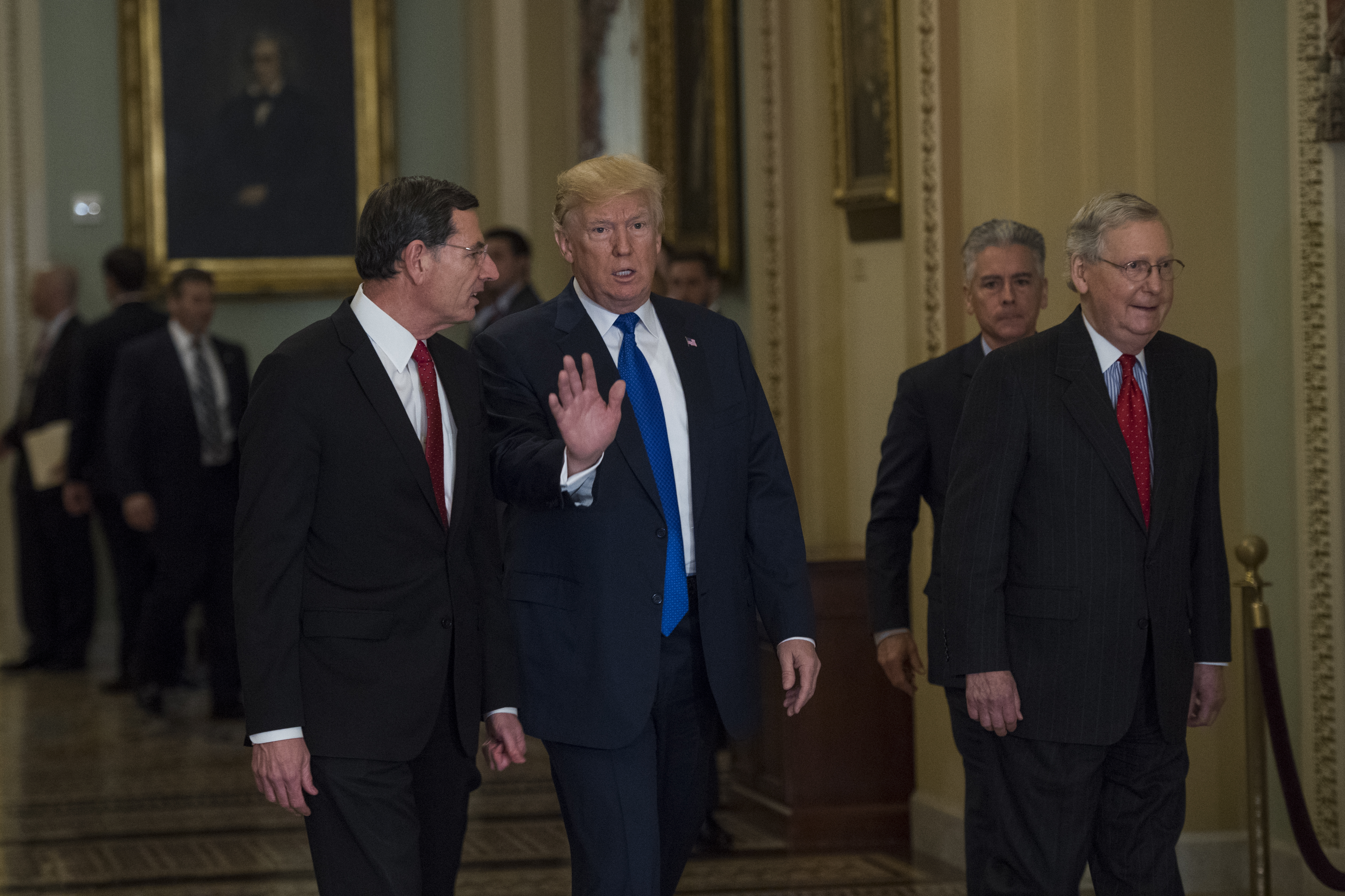 President Donald Trump arrives with Sen. John Barrasso, R-Wyo., left, and Senate Majority Leader Mitch McConnell, R-Ky., for the Republican Senate Policy luncheon in the Capitol to discuss the tax reform bill on November 28, 2017.