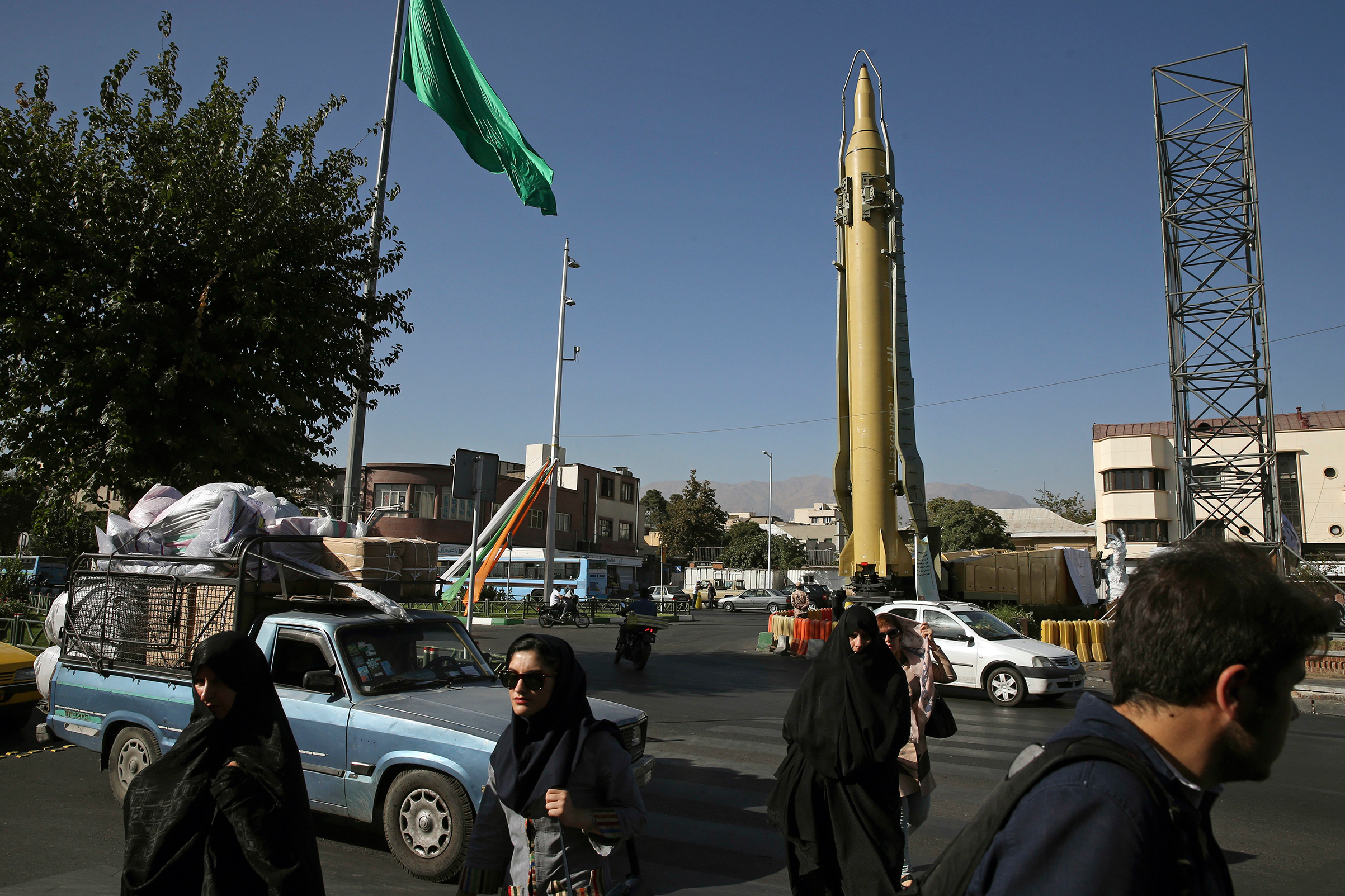 Iranians walk past a Ghadr-F missile displayed at a Revolutionary Guard hardware exhibition, marking 36th anniversary of the outset of Iran-Iraq war, in downtown Tehran on Sept. 25, 2016.