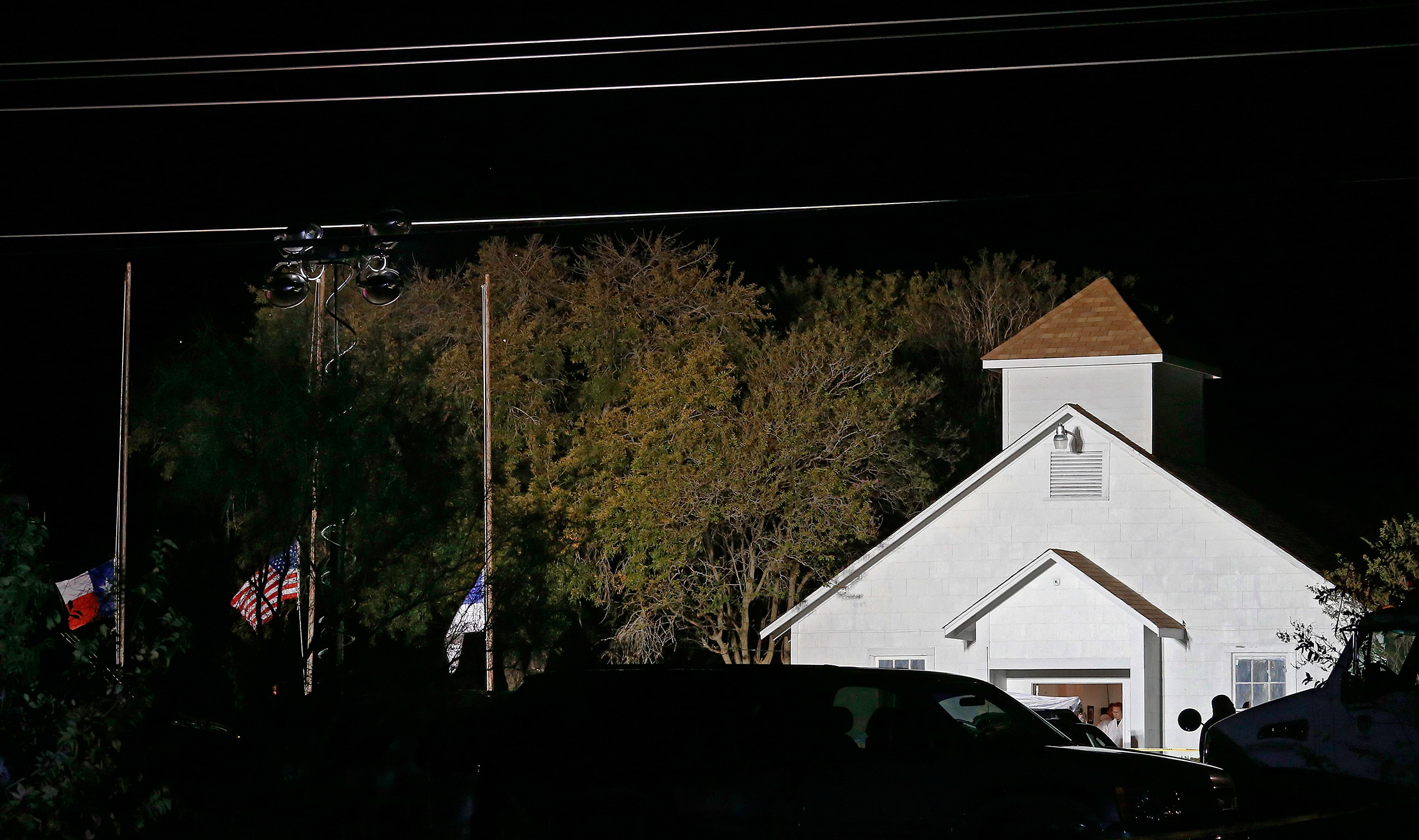 The First Baptist Church in Sutherland Springs is illuminated by raised lamps as investigators work, hours after the shooting on Nov. 5