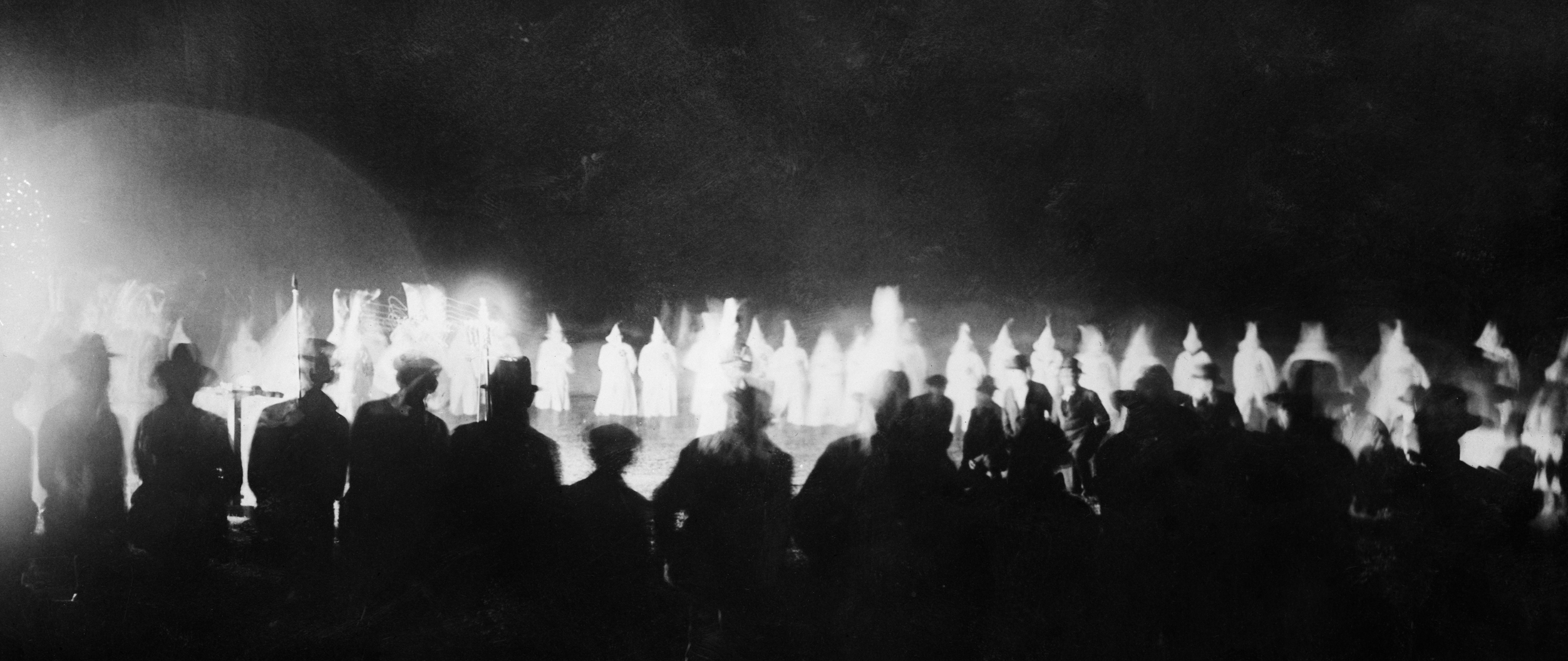 Onlookers watch as the Ku Klux Klan initiates new members at a Miami golf course in the 1920s.
