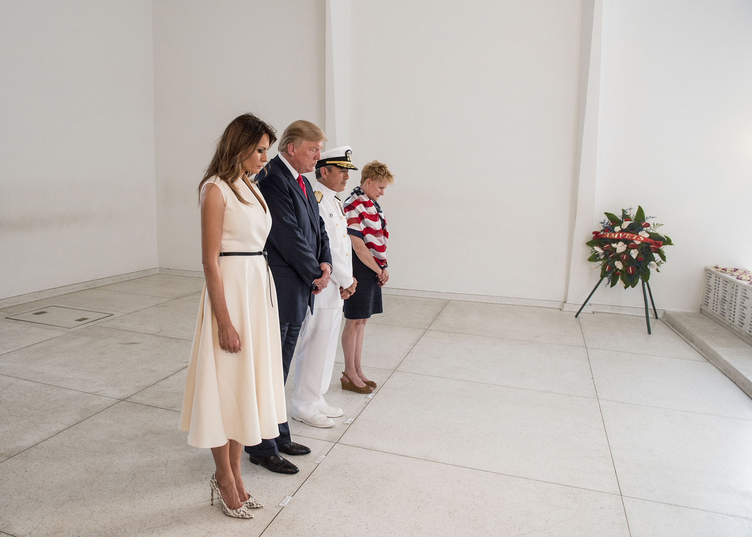 First Lady Melania Trump, wearing a Christian Dior dress and Manolo Blahnik shoes, joins her husband, US Pacific Command Commander, Adm. Harry Harris, and his wife Ms. Bruni Bradley, to honor fallen service members at the USS Arizona Memorial at Pearl Harbor, Hawaii, on Nov. 3, 2017.