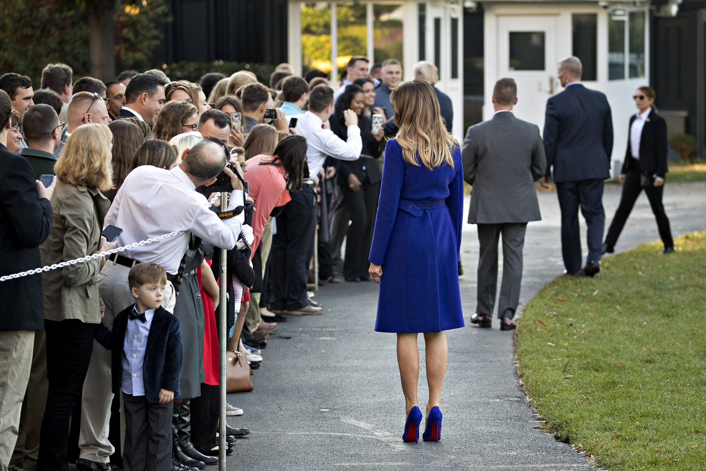 First Lady Melania Trump wearing a cobalt Pucci coat and matching Christian Louboutin shoes stands while greeting visitors before boarding Marine One on the South Lawn of the White House in Washington, on Nov. 3, 2017.