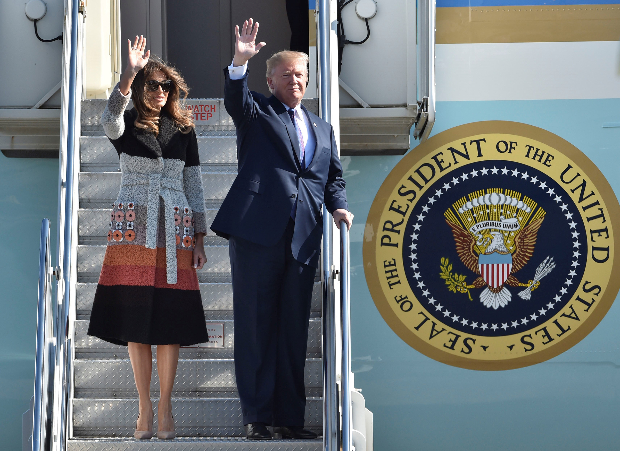 First lady Melania Trump, wearing a striped Fendi coat with floral embellishments, waves as she arrives at Yokota Air Base with her husband in Tokyo, Japan on Nov. 5, 2017.