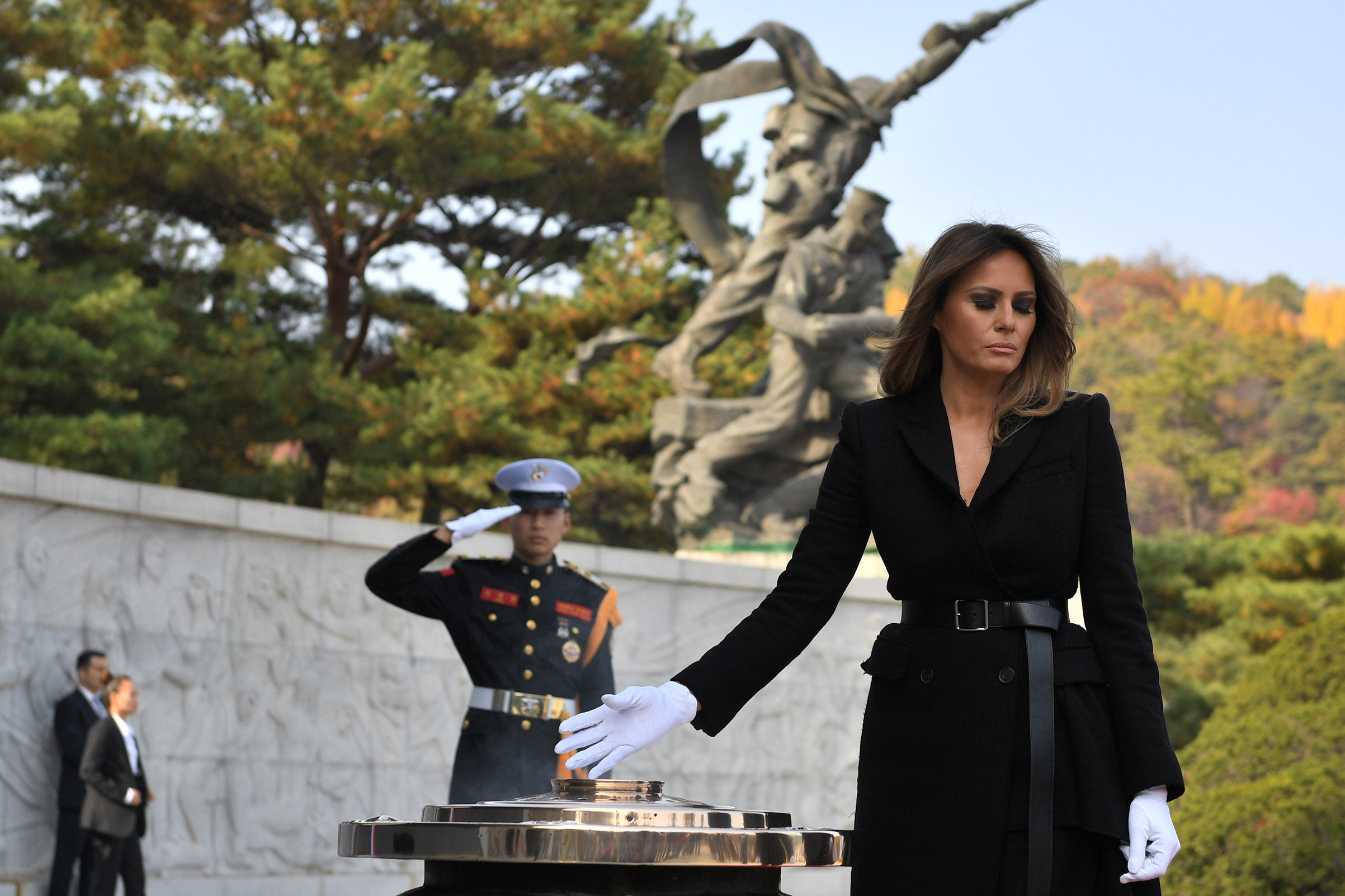 First Lady Melania Trump wearing a black belted coat, burns incense at the National Cemetery in Seoul on Nov. 8, 2017.