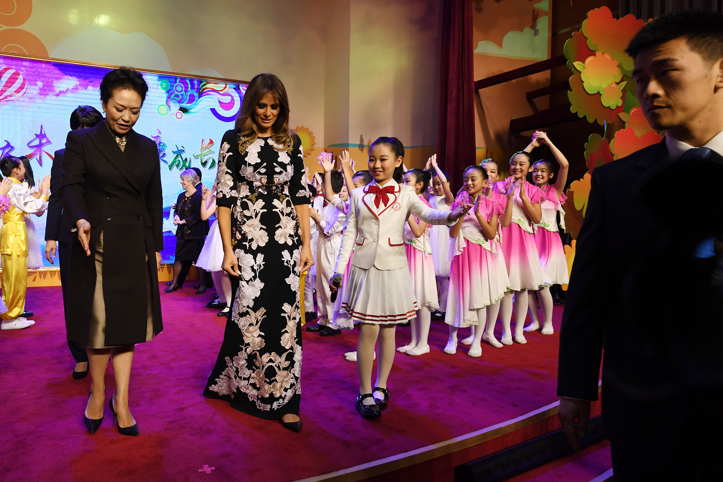 First Lady Melania Trump, wearing a custom Dolce & Gabbana gown, and China's First Lady Peng Liyuan are escorted by a student after a cultural performance during a visit to Banchang Primary School in Beijing on Nov. 9, 2017.