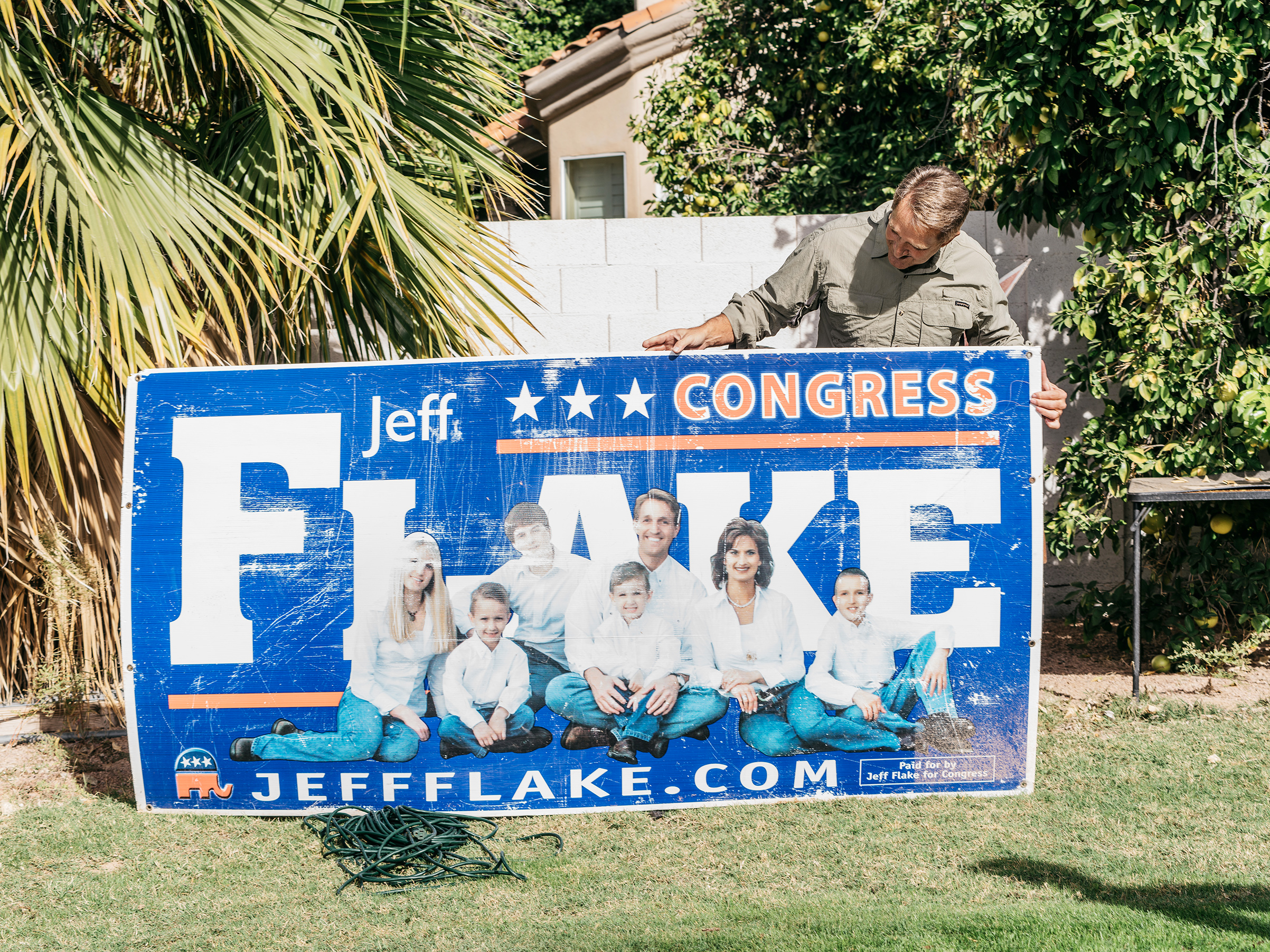 Flake holds an old campaign sign in his backyard, Mesa, Ariz.