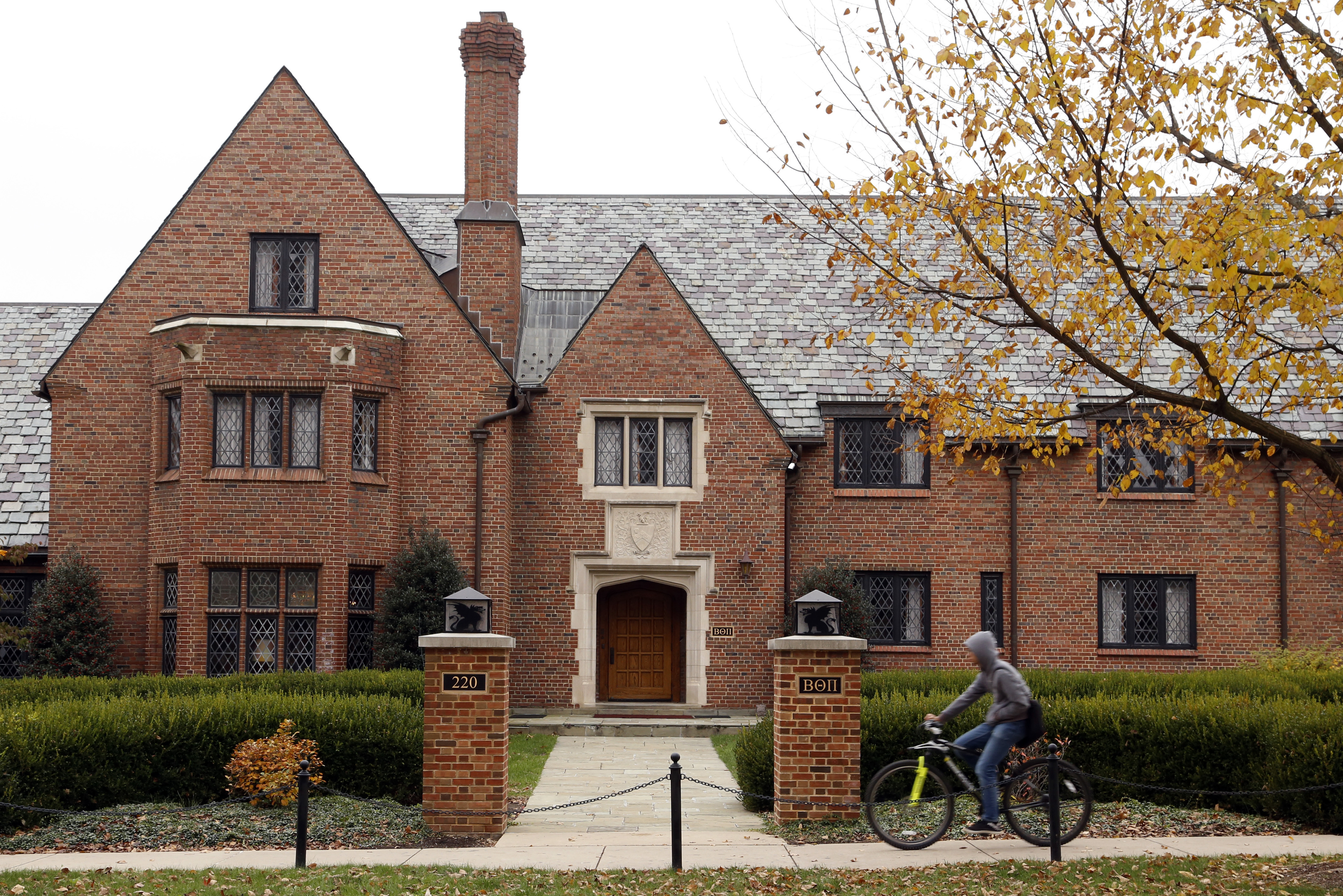 A bicyclist rides past Pennsylvania State University's shuttered Beta Theta Pi fraternity house on Nov. 9, 2017, in State College, Pa.