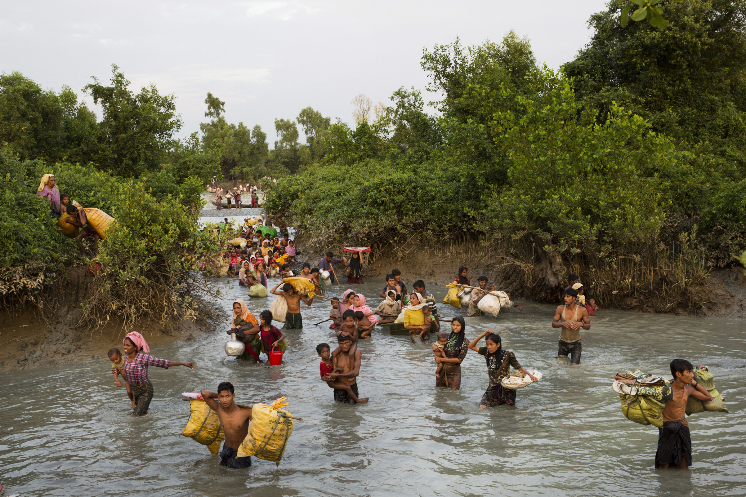 Rohingya wade through the Naf River after having just crossed over from Myanmar into Bangladesh, near Palong Khali, Bangladesh, on Nov. 1, 2017.