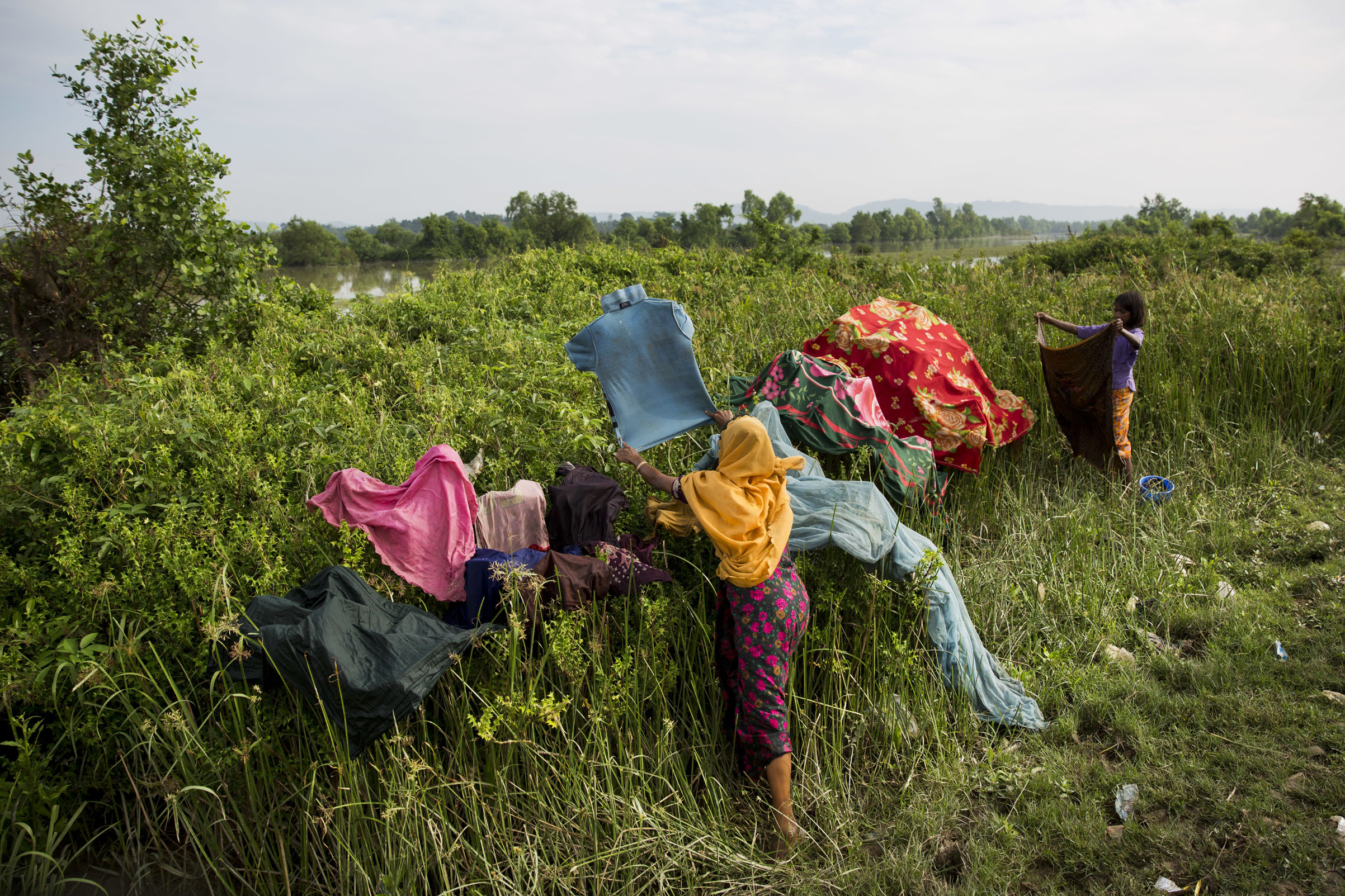 Rohingya dry their clothes as they wait along the border after crossing the Naf River near Palong Khali, Bangladesh, on Nov. 2, 2017.