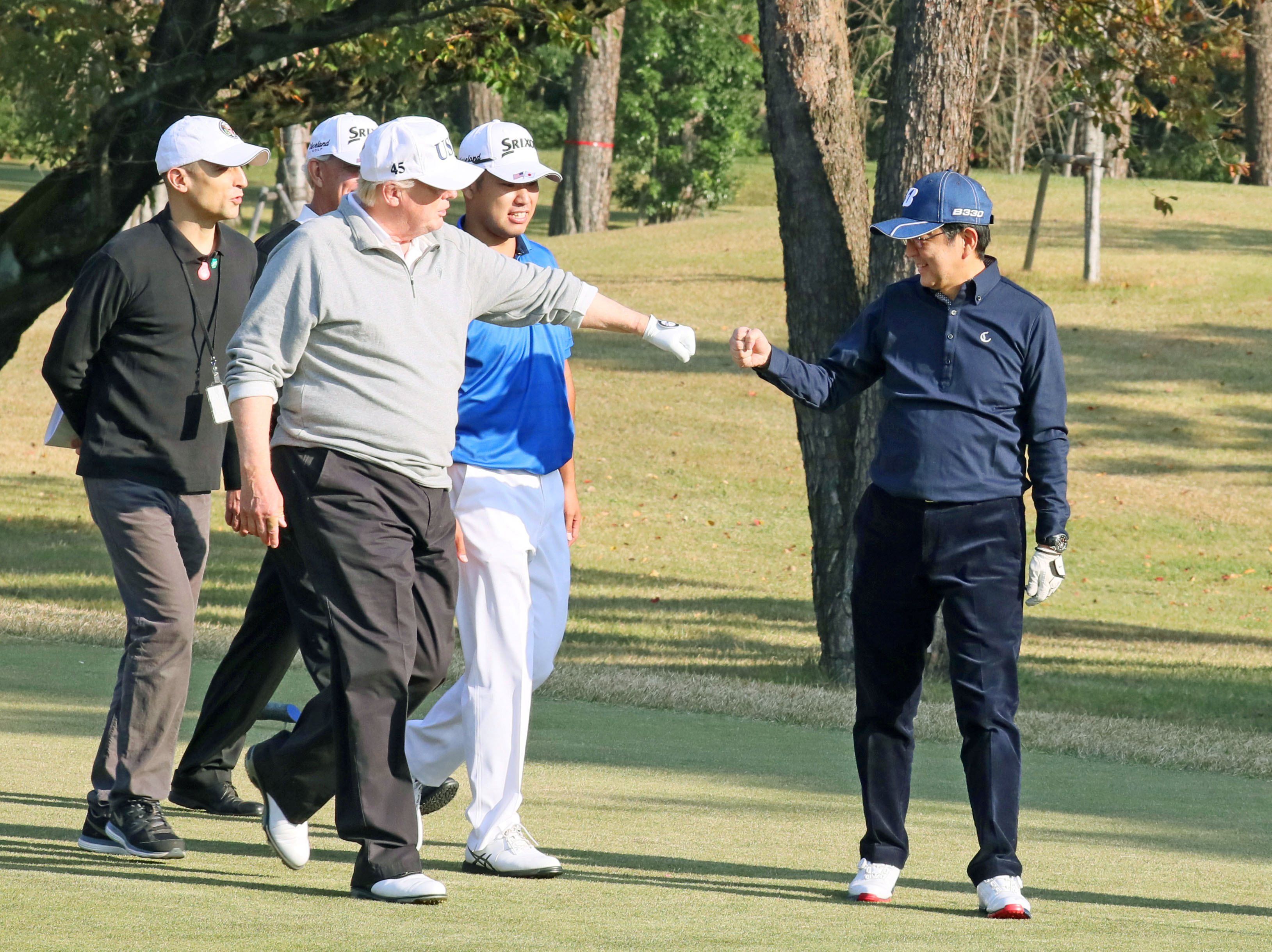 President Donald Trump share a fist bump with Japan's Prime Minister Shinzo Abe as they play golf at the Kasumigaseki Country Club north of Tokyo, Japan on Nov. 5, 2017.