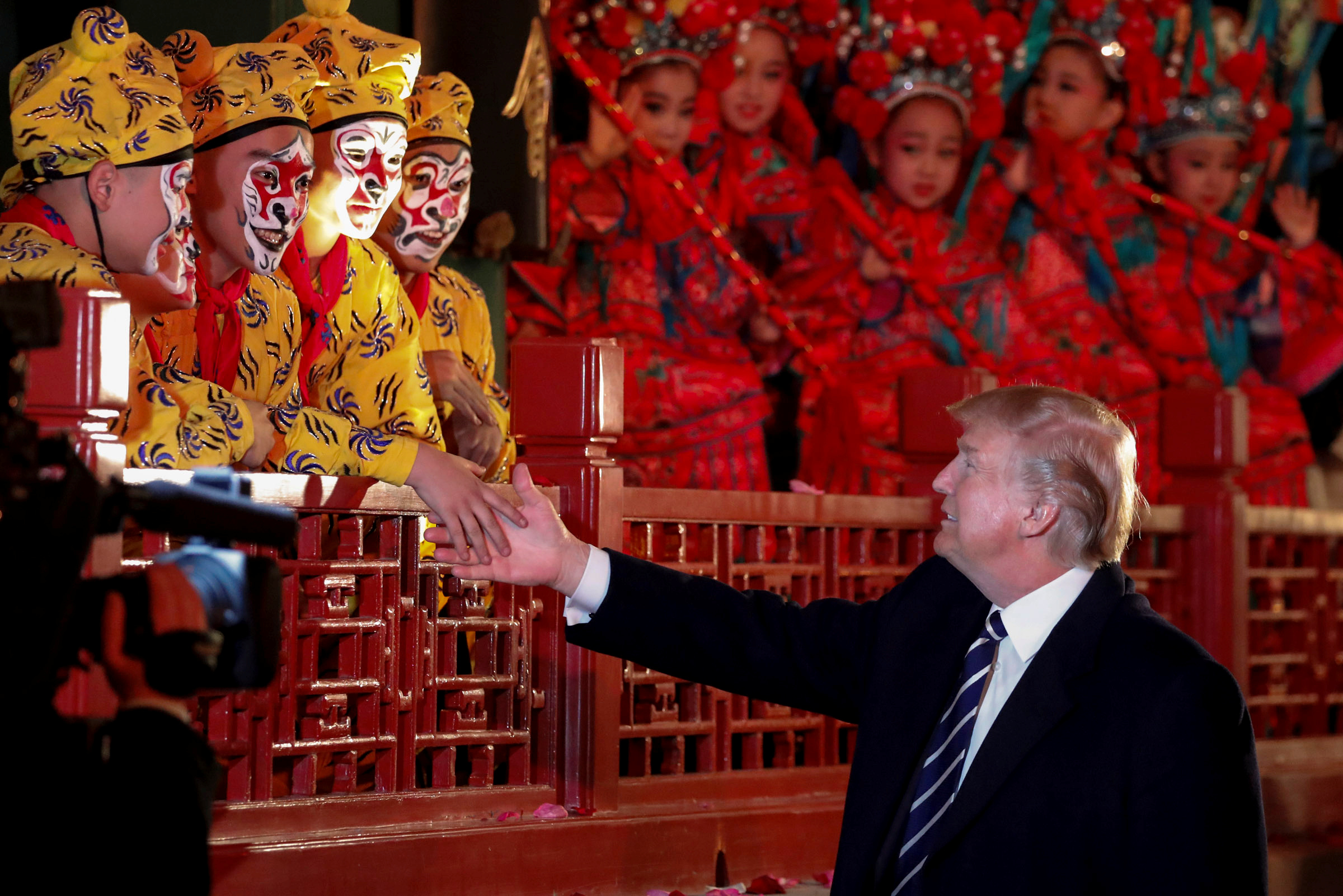 U.S. President Donald Trump shakes hands with opera performers at the Forbidden City in Beijing, China, on Nov. 8, 2017.
