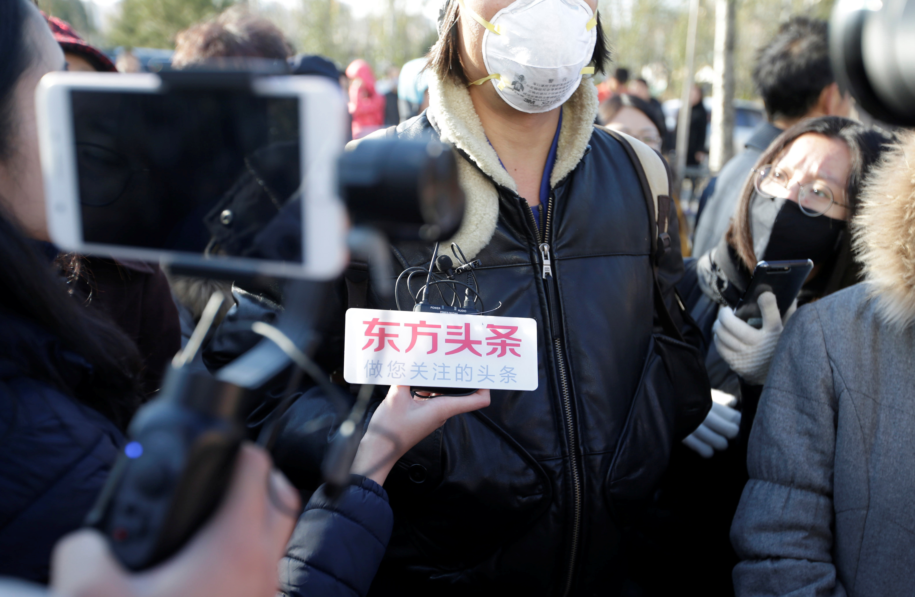 A parent is surrounded by members of the media outside the kindergarten run by pre-school operator RYB Education Inc being investigated by China's police, in Beijing, China Nov. 24, 2017.