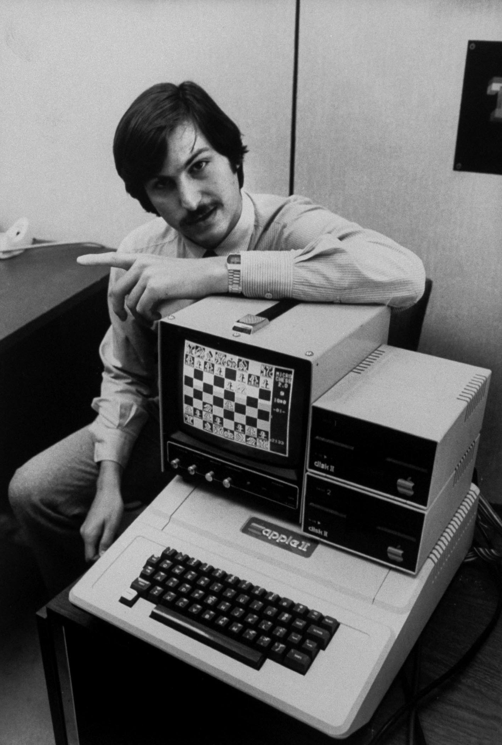 Steve Jobs with Apple II computer, with chess game displayed on screen.