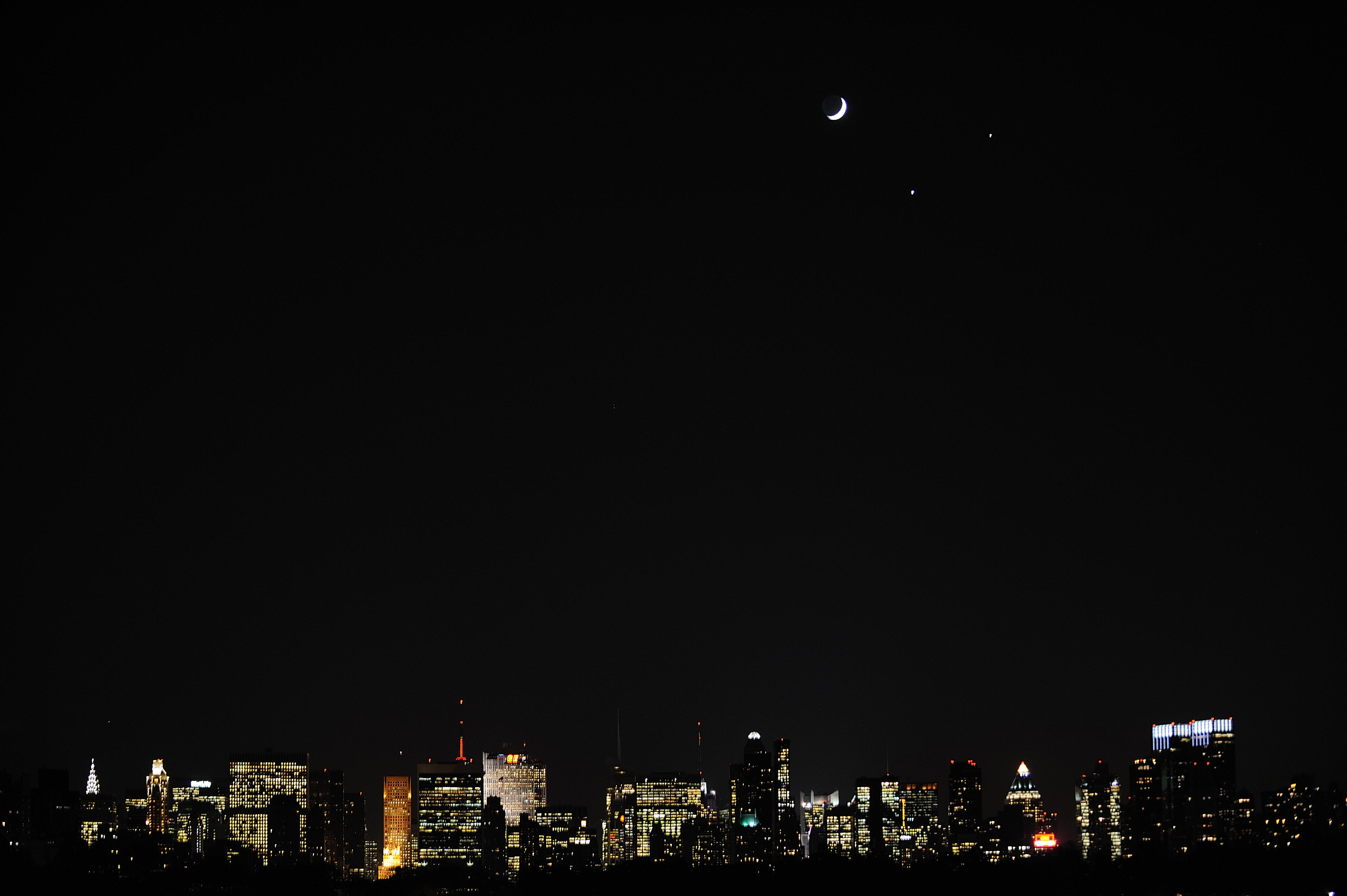 A crecent moon (L) and the planets Venus (C, bottom) and Jupiter (R) are seen in a rare alignment over the Manhattan skyline on Dec. 1, 2008 from New York.