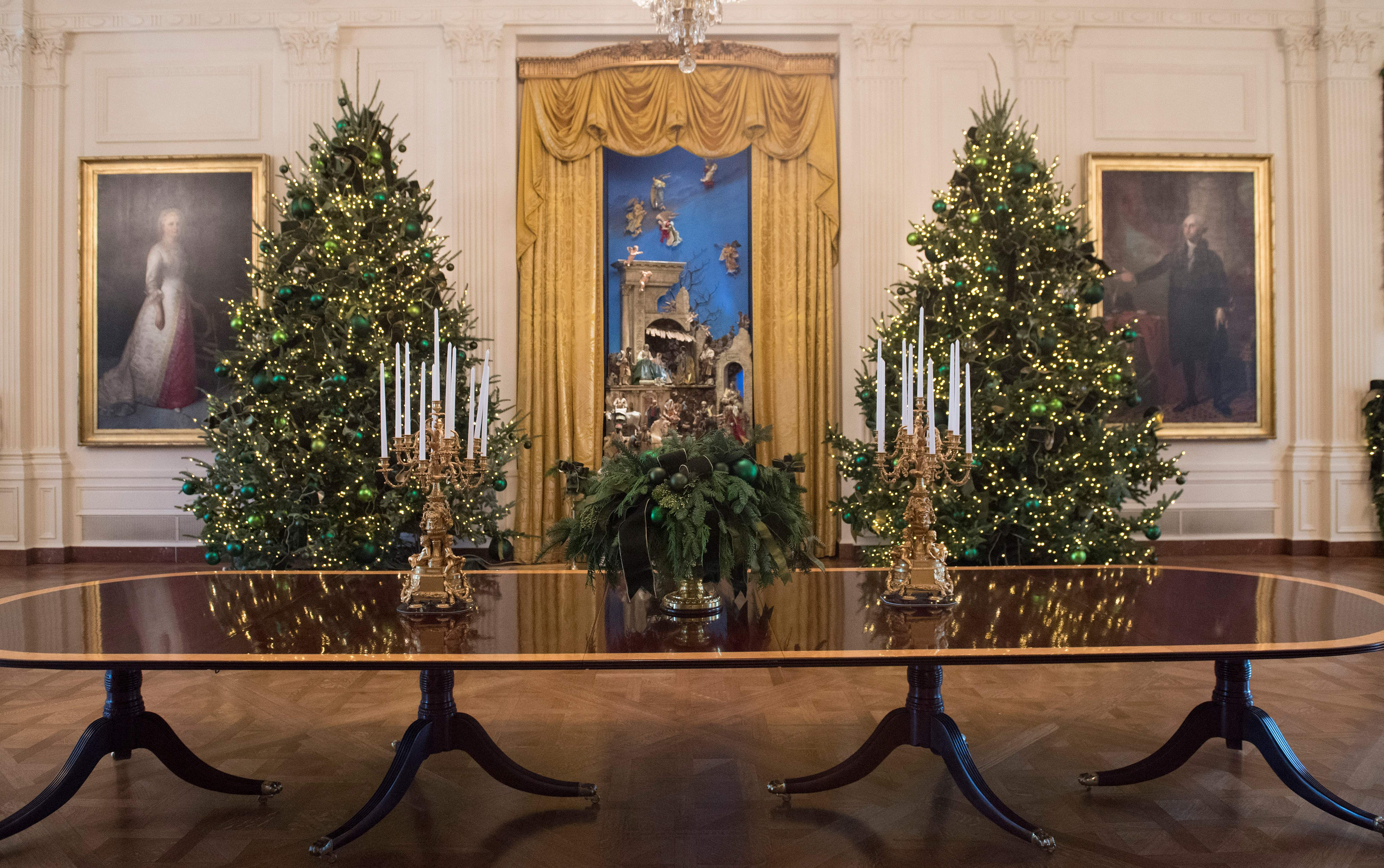 Christmas trees are seen during a preview of holiday decorations in the East Room of the White House in Washington, DC, November 27, 2017.