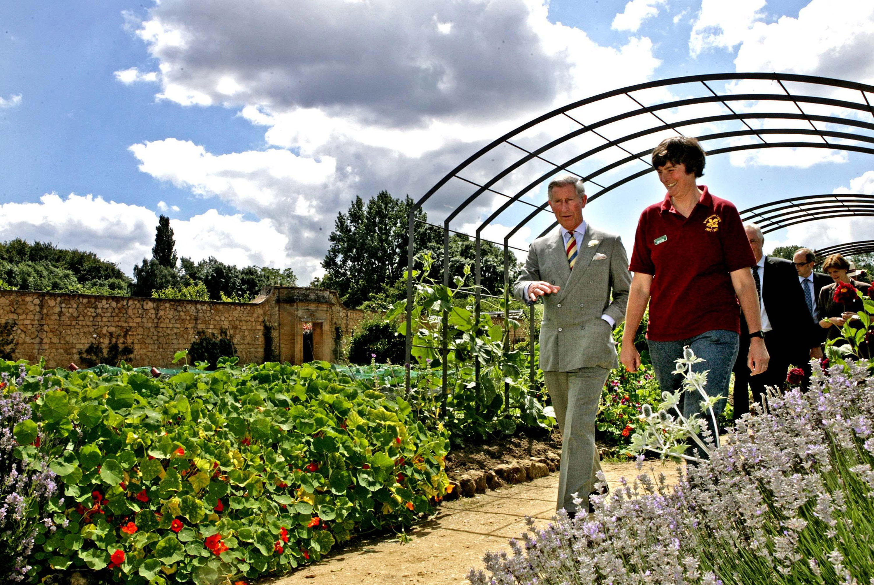 Prince Charles, Prince of Wales and head gardener Christine Brain tour the Gertrude Jekyll inspired Arts and Crafts Garden at Barrington Court on July 18, 2007 in Barrington, England. (Photo by Pool/Anwar Hussein Collection/WireImage)