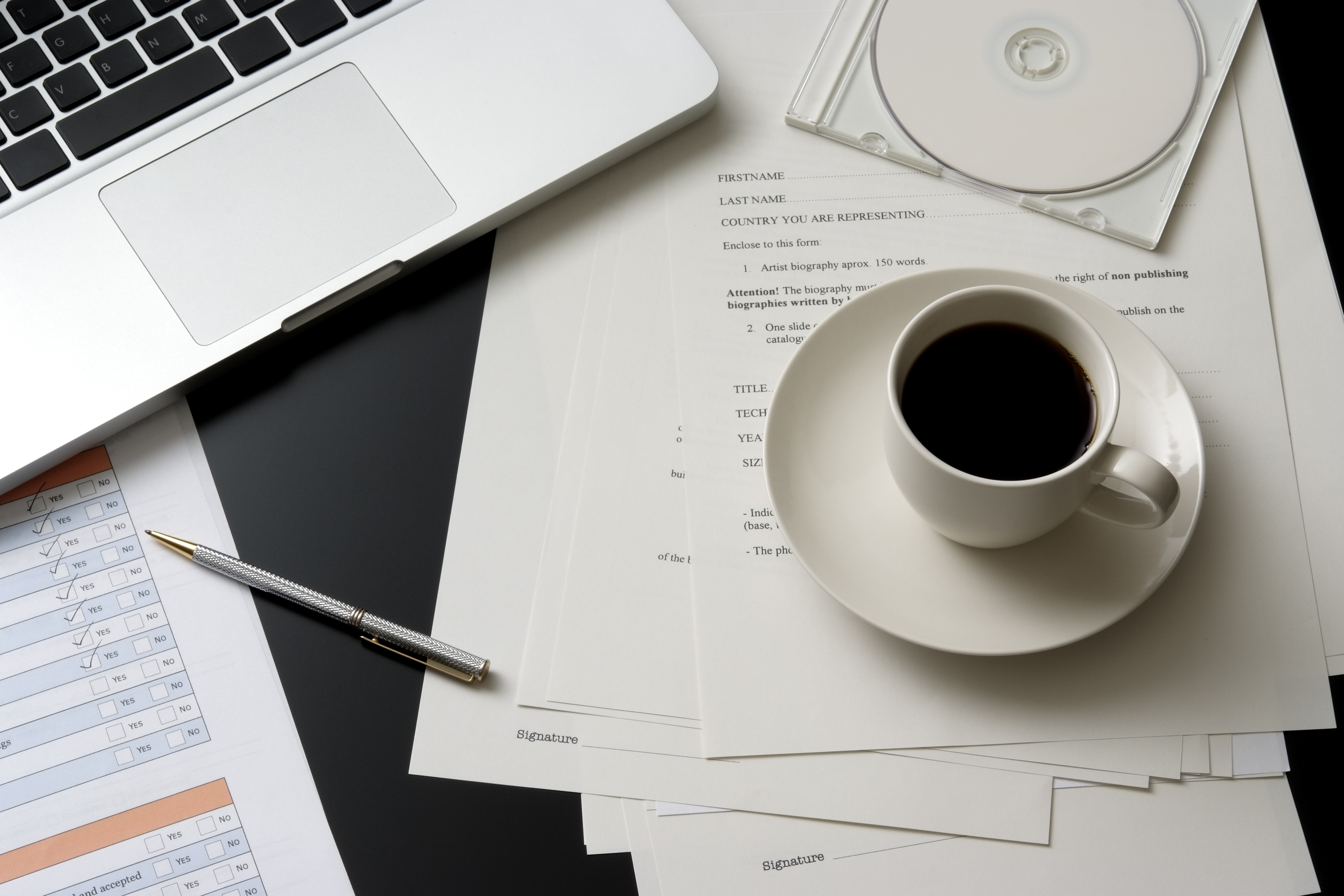 A close up of a desk at a business office.  This desk includes a cup of black coffee served in a white cup on a white saucer, a laptop computer a pair of DVD and document.