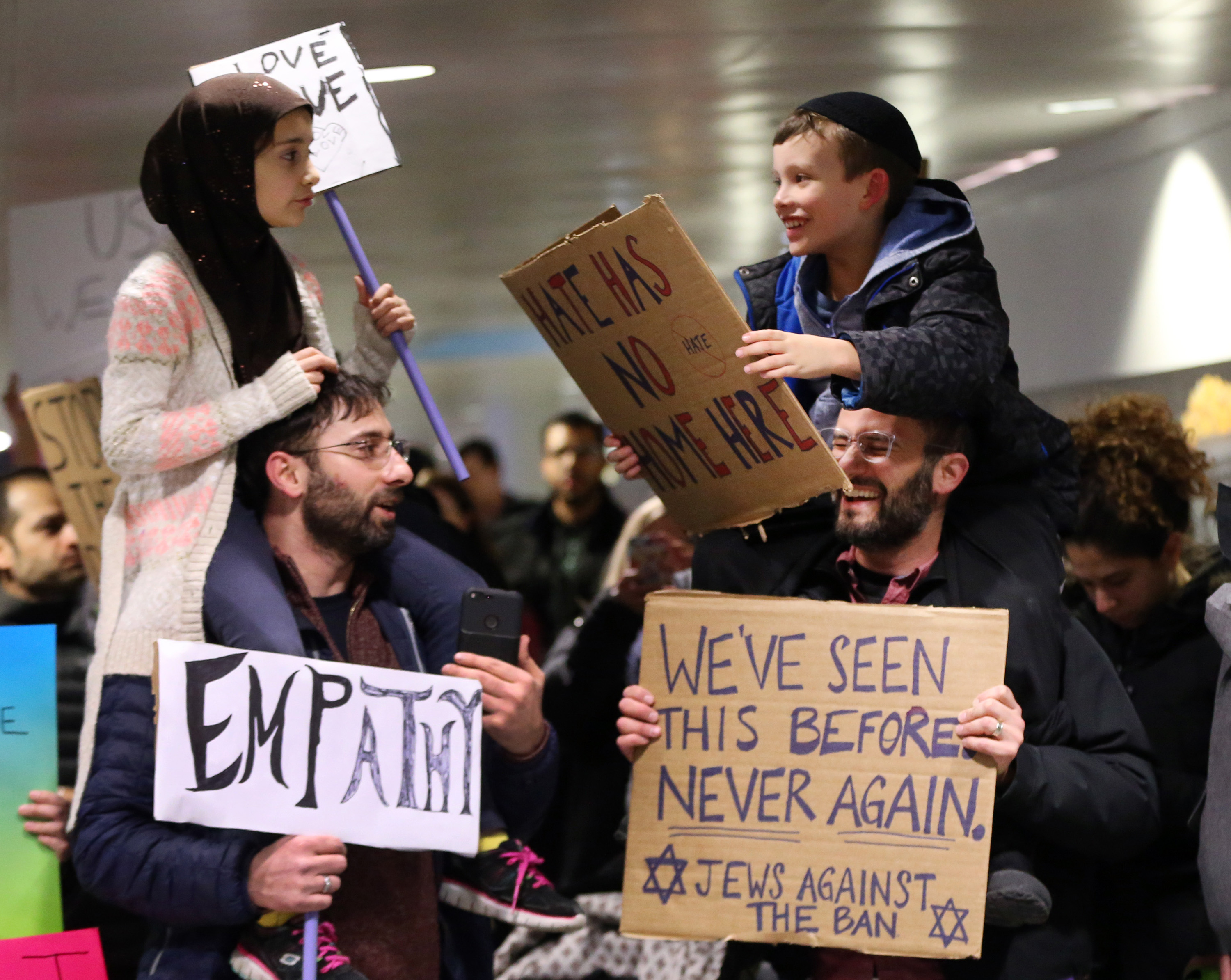 A smiley shot of a young girl in a hijab and a little boy in a kippah peacefully protesting President Donald Trump's immigration order made headlines and was reteweeted 13,000 times across the internet as people celebrated. Sitting on the shoulders of their fathers: Meryem Yildirim, 7, and Adin Bendat-Appell, 9 carried the signs:  Love Love Love  and  Hate Has No Home Here  at O'Hare International Airport in Chicago, Ill. Captured at a decisive moment by the Chicago Tribune's  Nucci DiNuzzo, people praised the universality of its message.