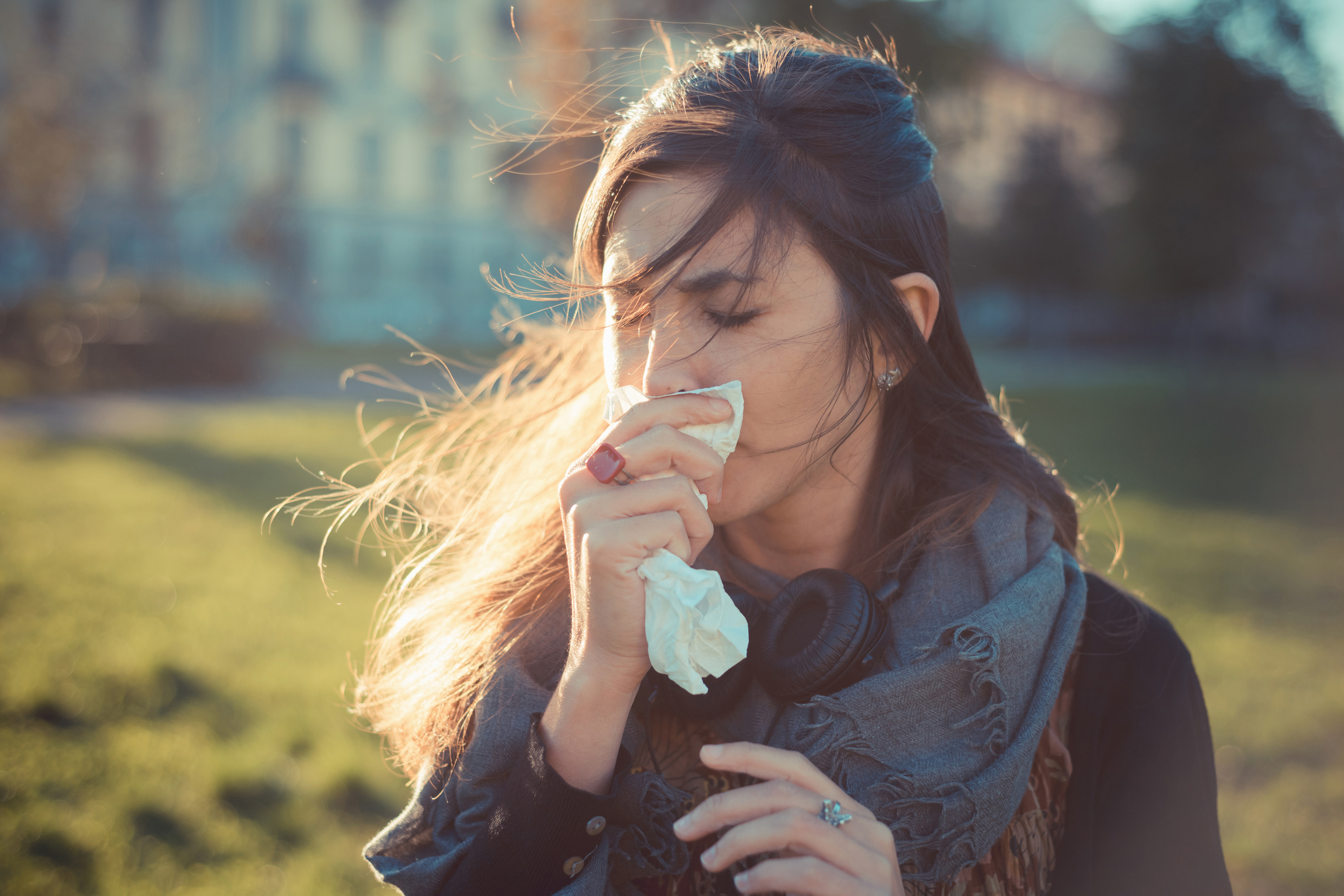 Mid adult woman blowing nose with hankerchief in park