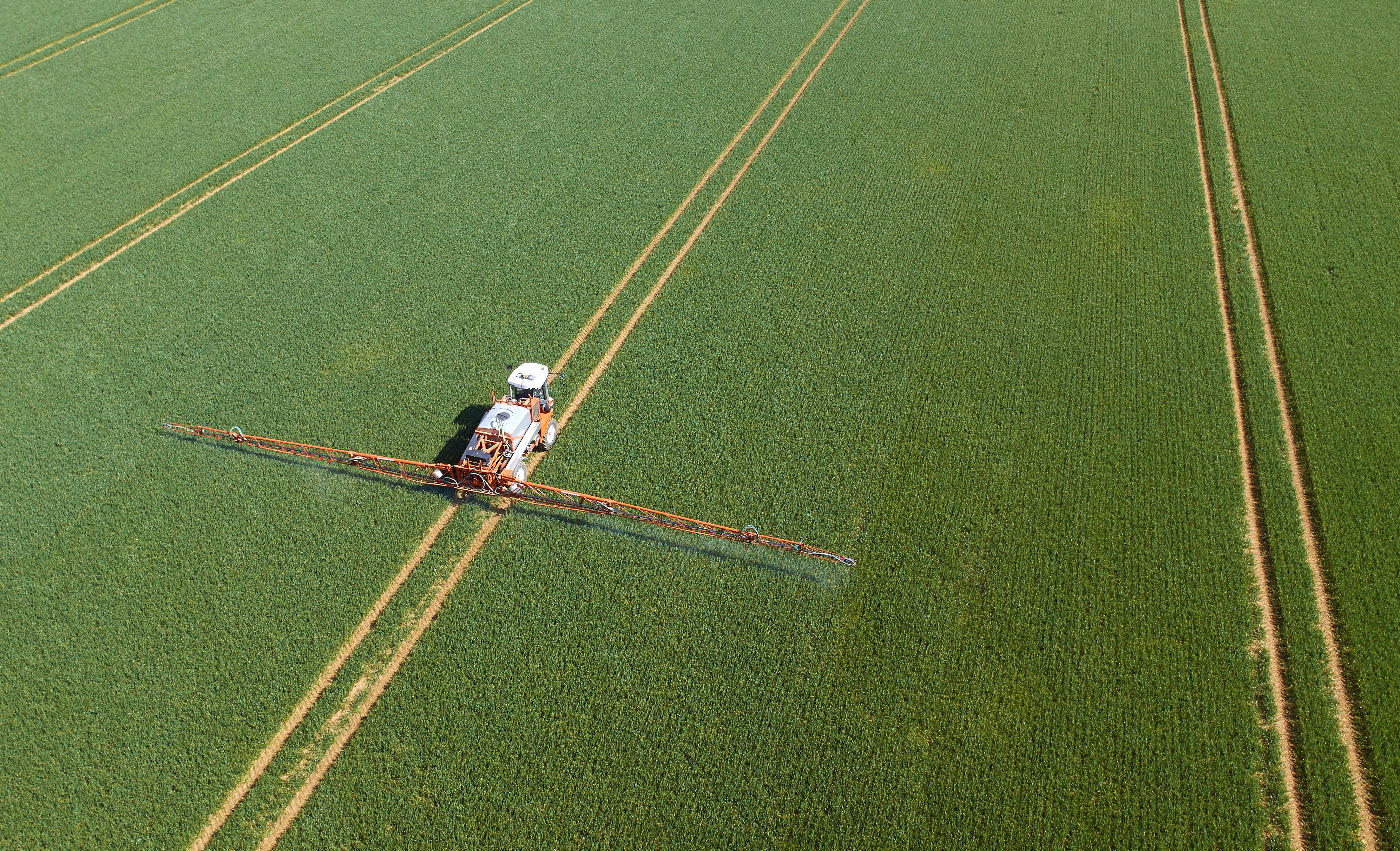 Crop sprayer in field aerial view - Captured by a licensed UAV operator with a permission for aerial work.
