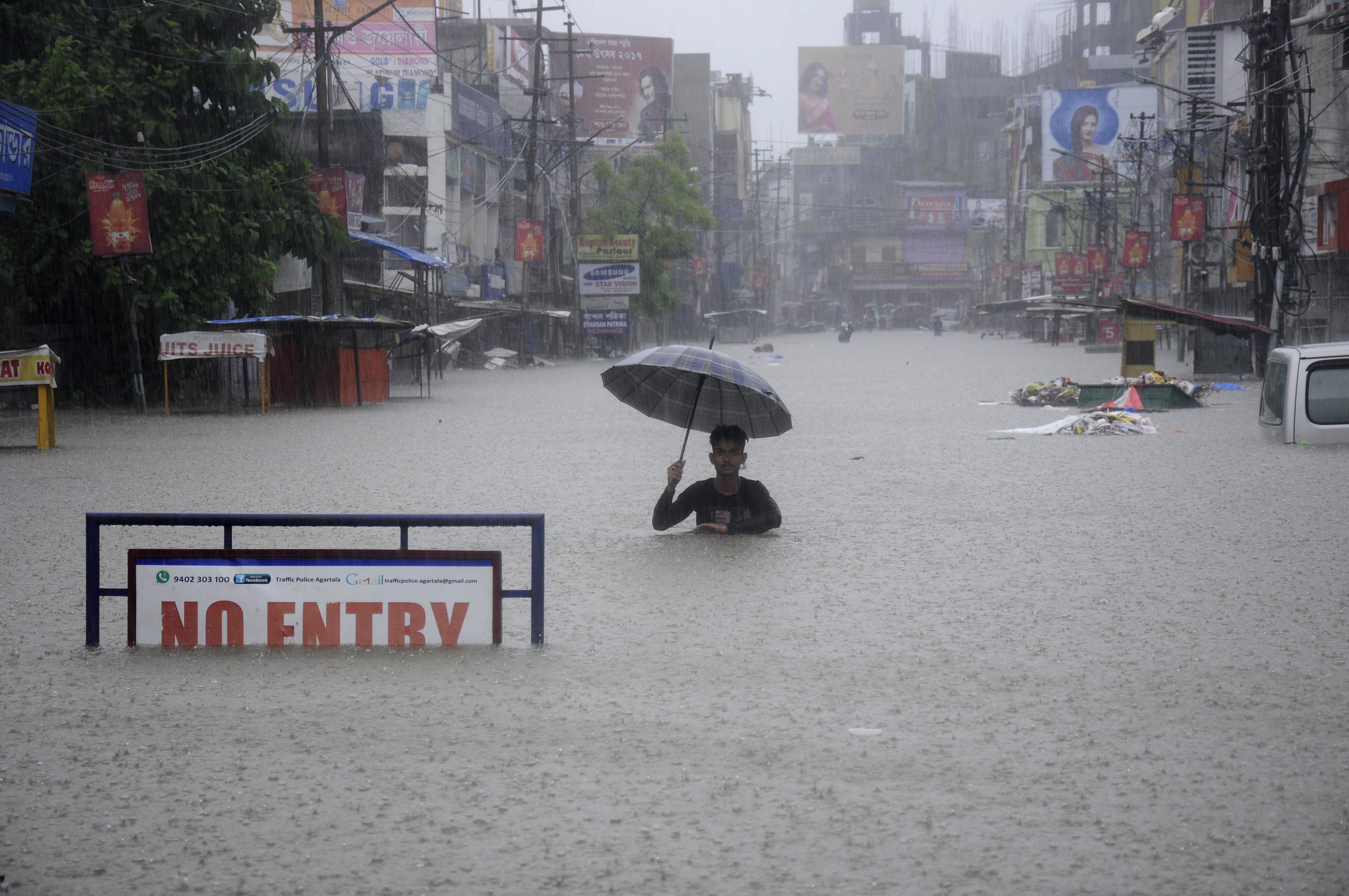 An Indian man wades along a flooded street during a heavy downpour in Agartala, the capital of northeastern state of Tripura, on August 11, 2017.
