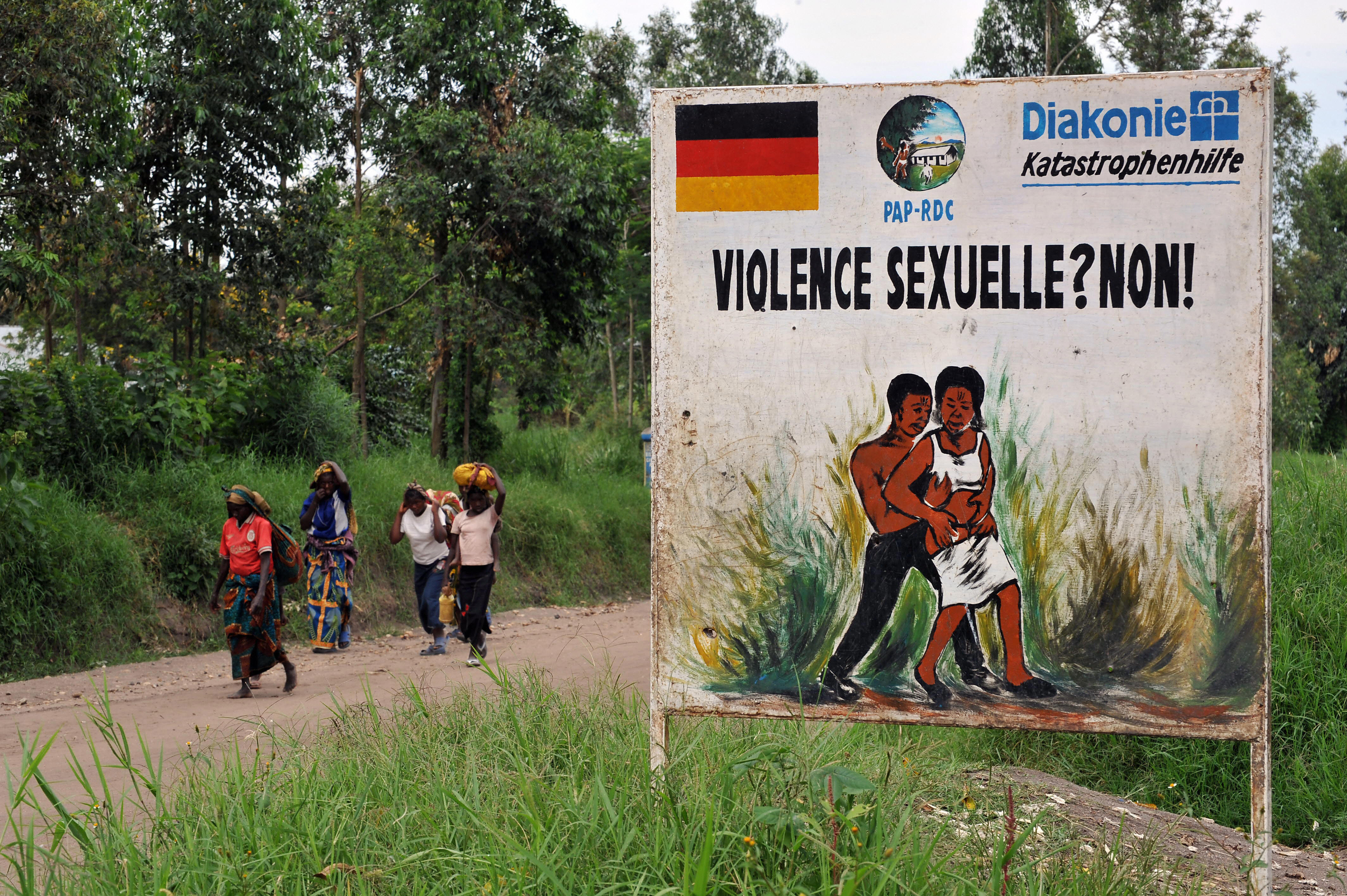 Congolese women walk past a sign opposing sexual violence on Dec.. 4, 2008 in Nyamilima, in Nord-Kivu, in the east of the Democratic Republic of Congo (DRC).